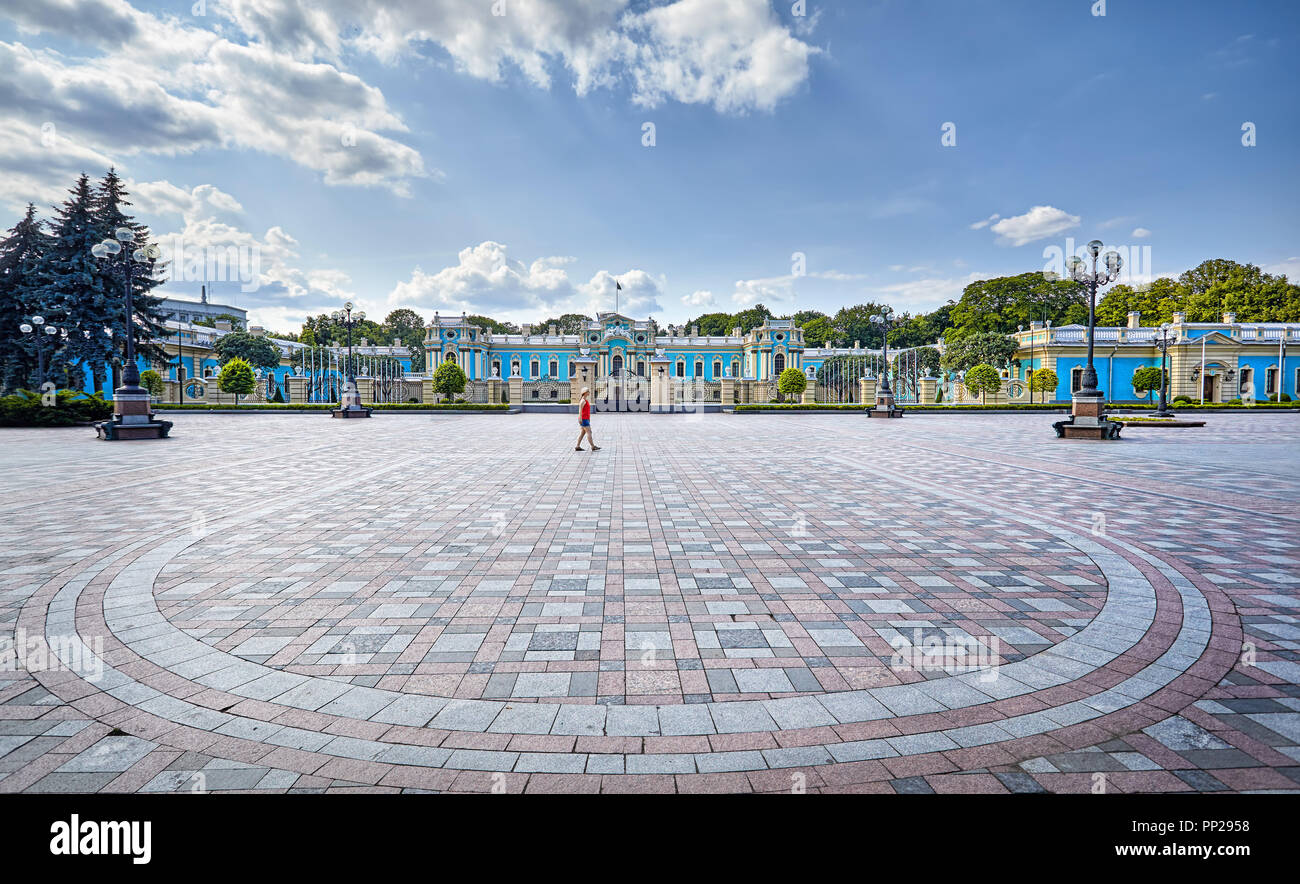 Woman in red shirt walking in front of Mariinsky Palace on sunny day, Kiev, Ukraine - Stock Image