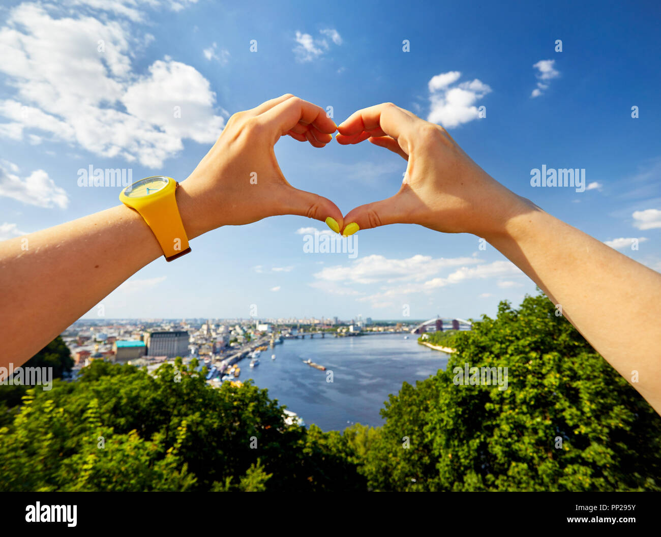 Woman hands in shape of heart with yellow watch against panorama of Kiev city downtown in Ukraine - Stock Image