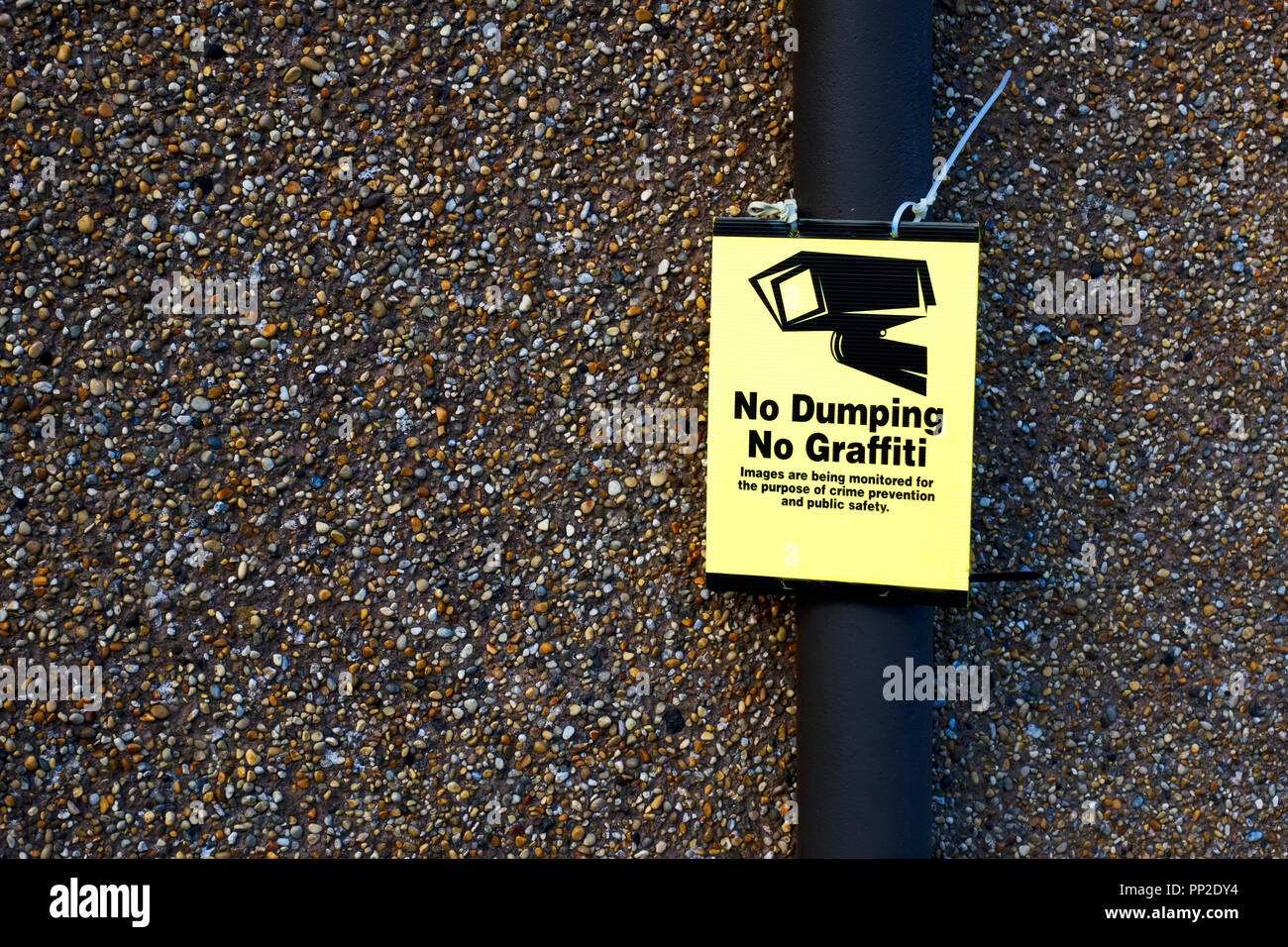 No dumping graffiti CCTV sign post and wall - Stock Image