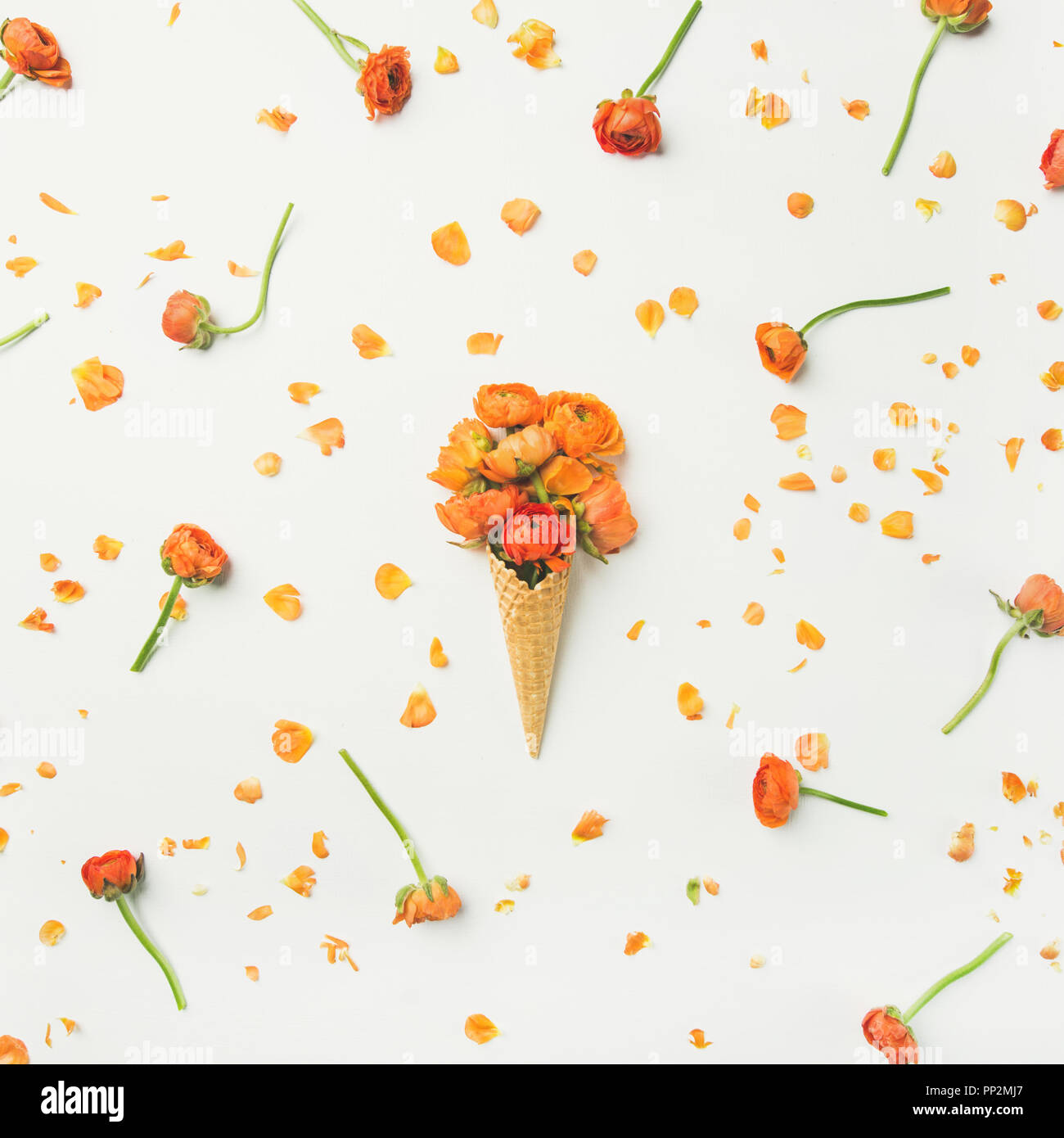 Waffle cone with orange buttercup flowers. Spring or summer mood concept - Stock Image