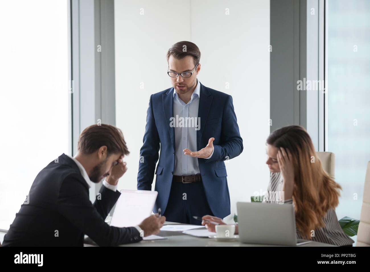 Mad businessman show dissatisfaction to partner at meeting - Stock Image