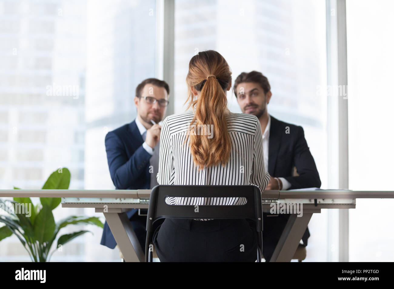 Female job candidate interview with doubting employers - Stock Image