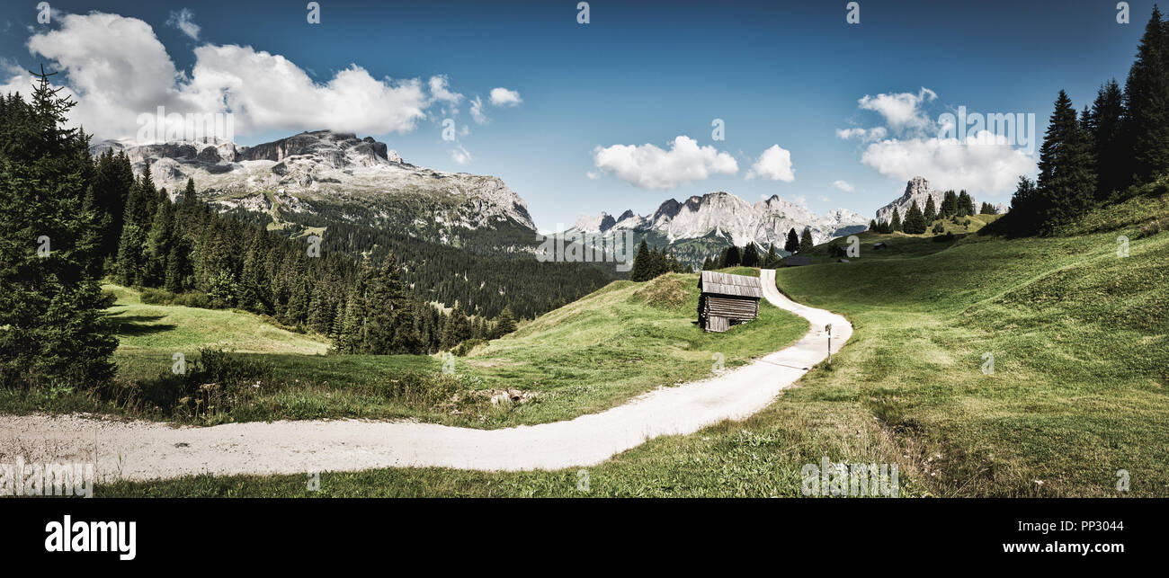 Vintage landscape of  mountains of Alta Badia in summer season with path in foreground and sky and clouds in background, Dolomites - Italy - Stock Image