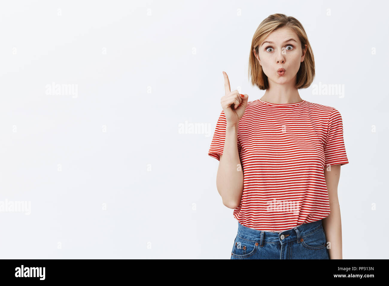Oh, one more thing. Beautiful girlfriend with clean screen and fair short haircut, raising index fingers in eureka gesture, folding lips curiously, adding interesting suggestion that came in mind - Stock Image