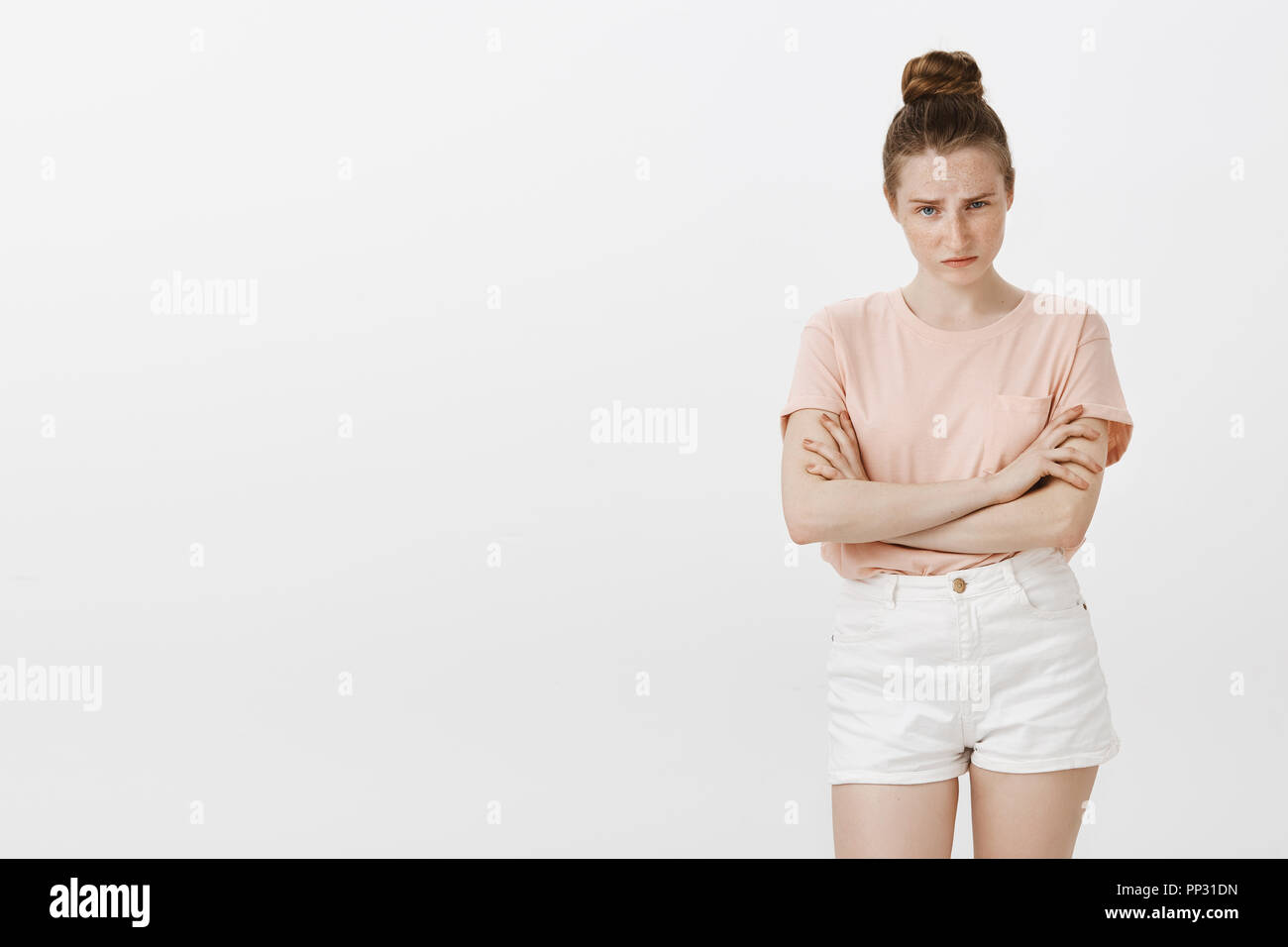 Girlfriend being suspicious, having disbelief. Portrait of intense unsure attractive woman in stylish pink t-shirt, lifting eyebrow, holding hands crossed, looking questioned at friend who telling lie - Stock Image