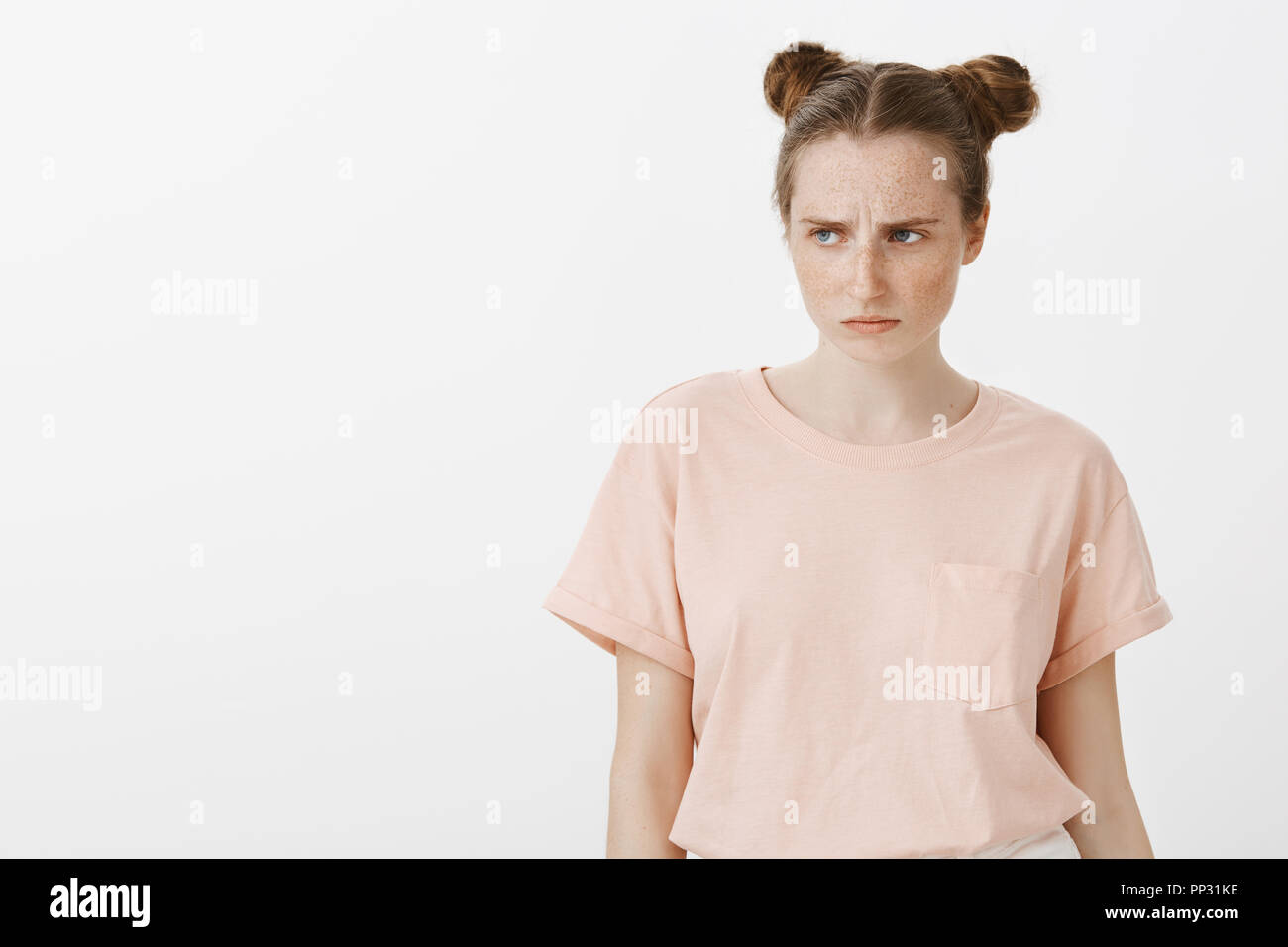 Girl feeling jealous and upset, wanting same toy as friend have. Portrait of offended gloomy woman in pink t-shirt, sulking and frowning while gazing left with regret and dislike over gray background - Stock Image