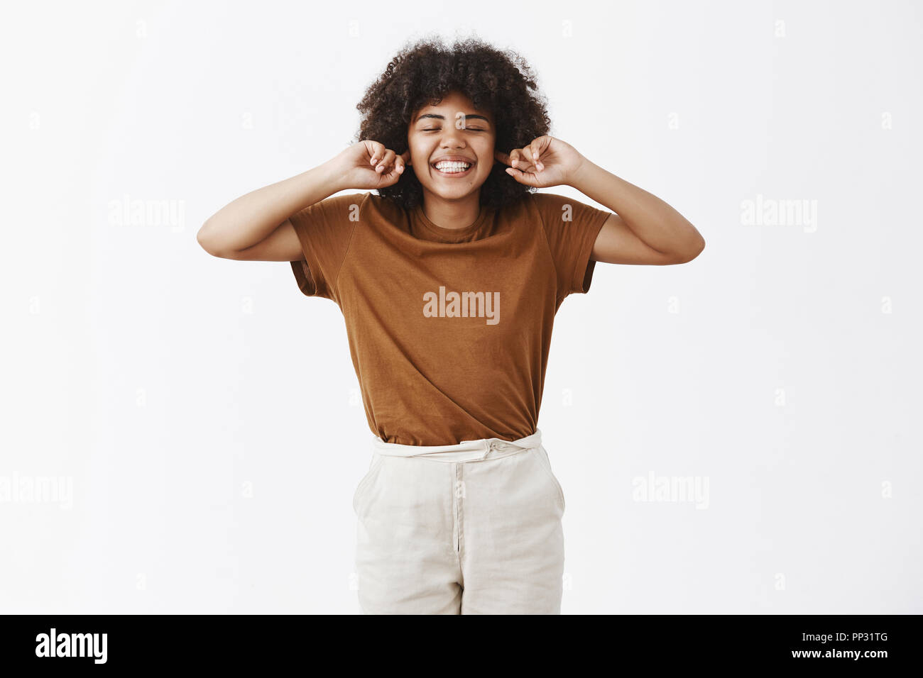Careless and happy attractive dark-skinned female student with curly hair in stylish outfit closing eyes and smiling with carefree indifferent expression covering ears with index fingers - Stock Image