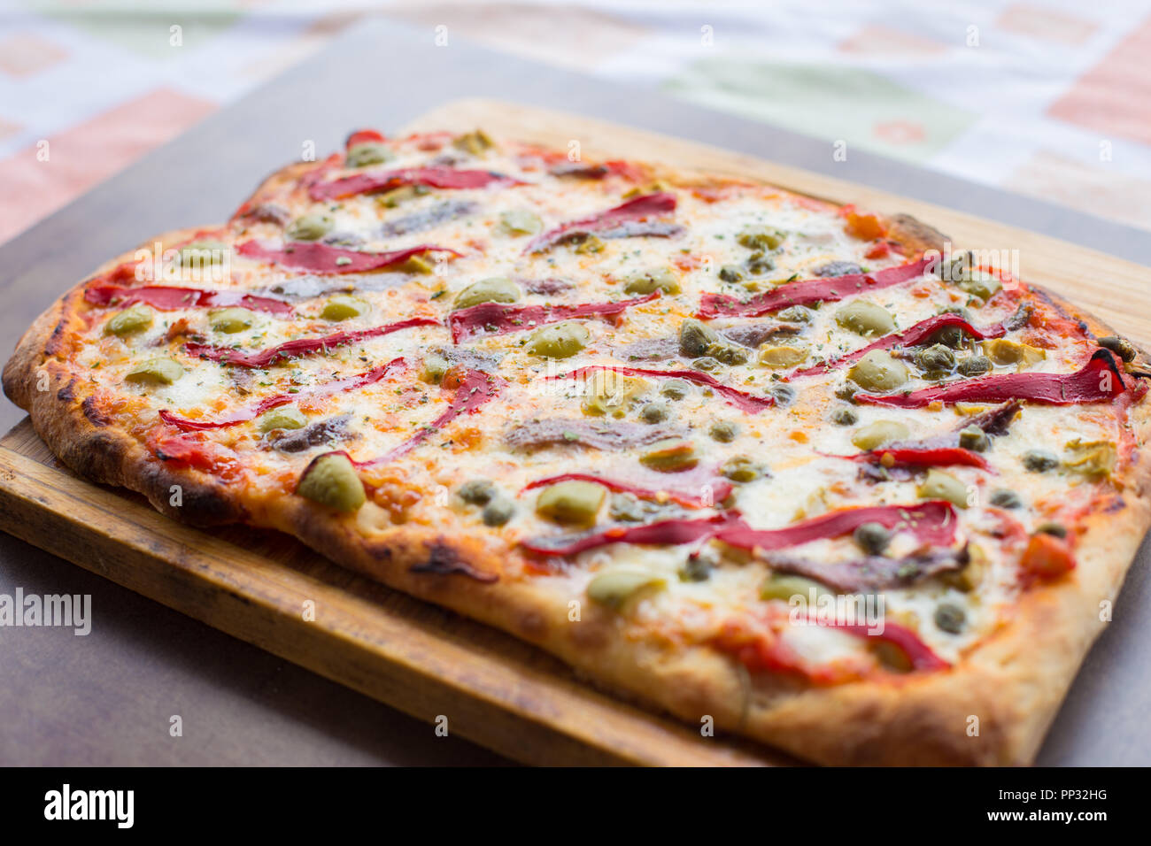 Homemade Italian pizza with anchovies, olives and capsicum. - Stock Image