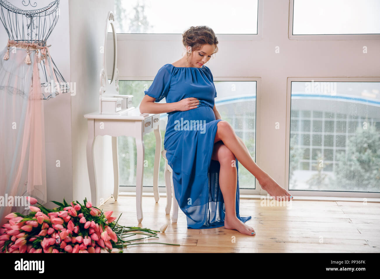 Pregnant woman surrounded by spring flowers sitting by the windows. in anticipation of the child. - Stock Image