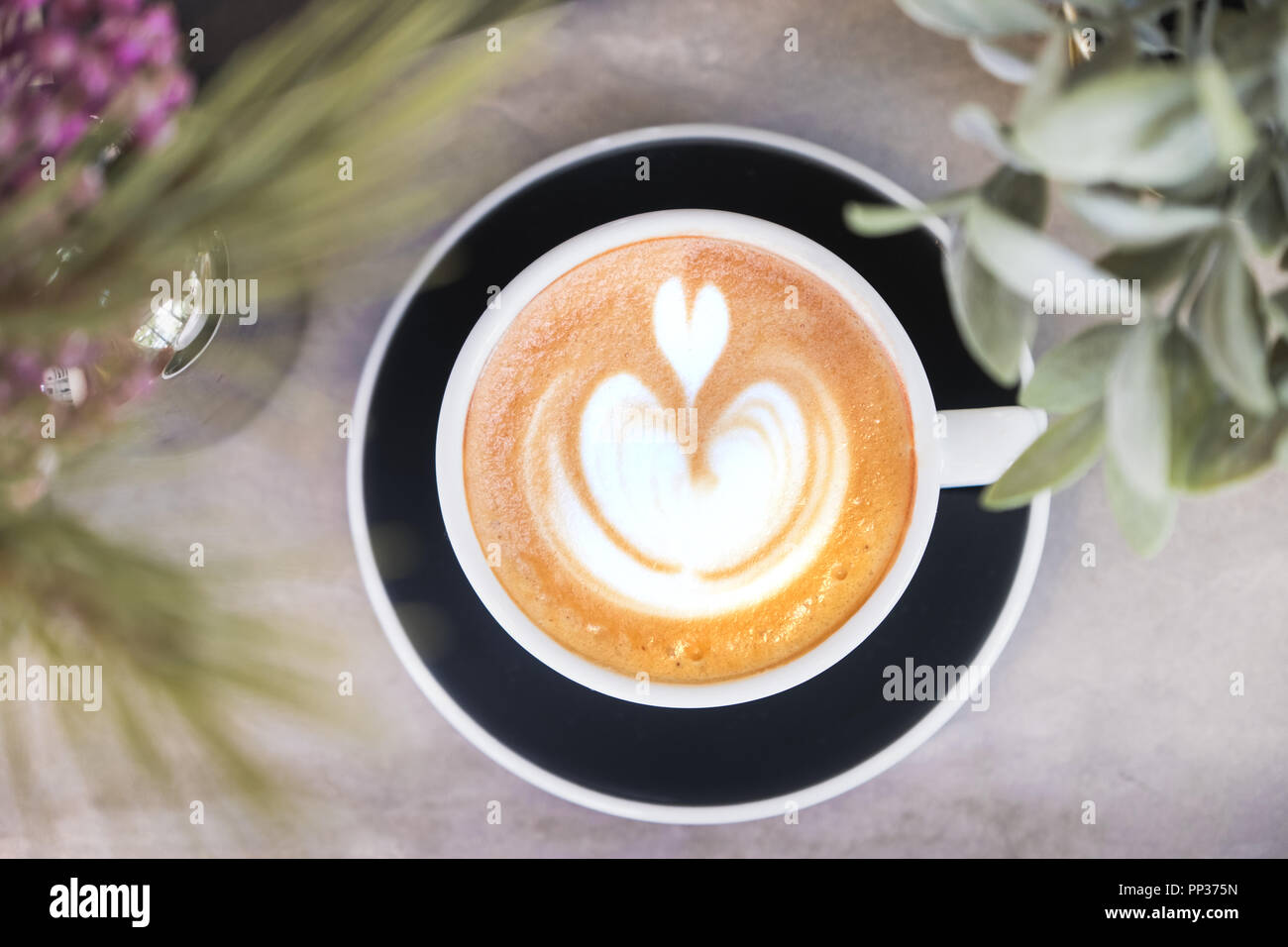 Top view of hot cappuccino coffee in black cup with latte art on grey concrete counter with green plant and floor foreground,Food and drink concept - Stock Image