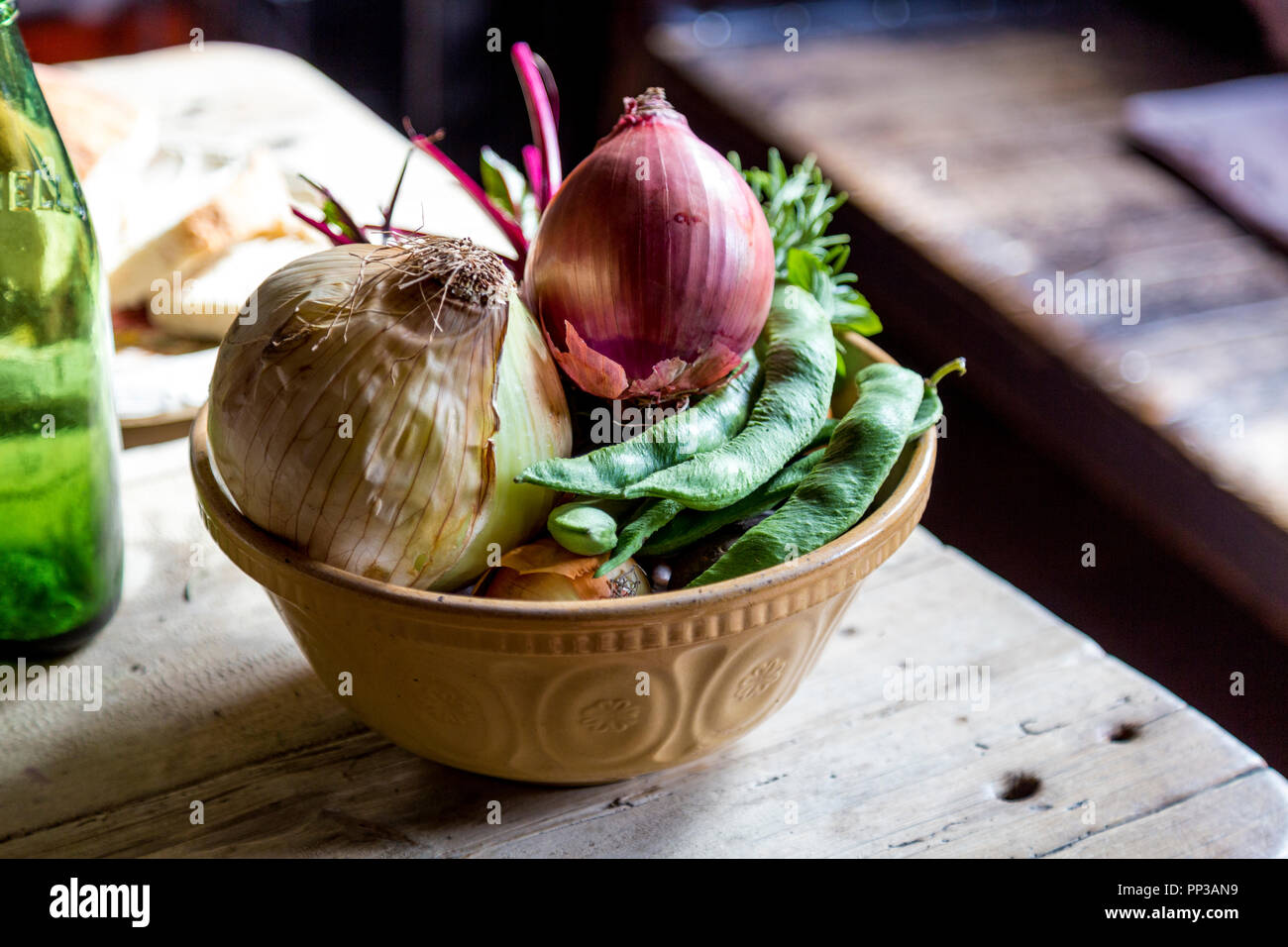 Rustic bowl of vegetables, onions and beans on a wooden table in an old-fashioned kitchen (Black Country Living Museum, Dudley, UK) - Stock Image
