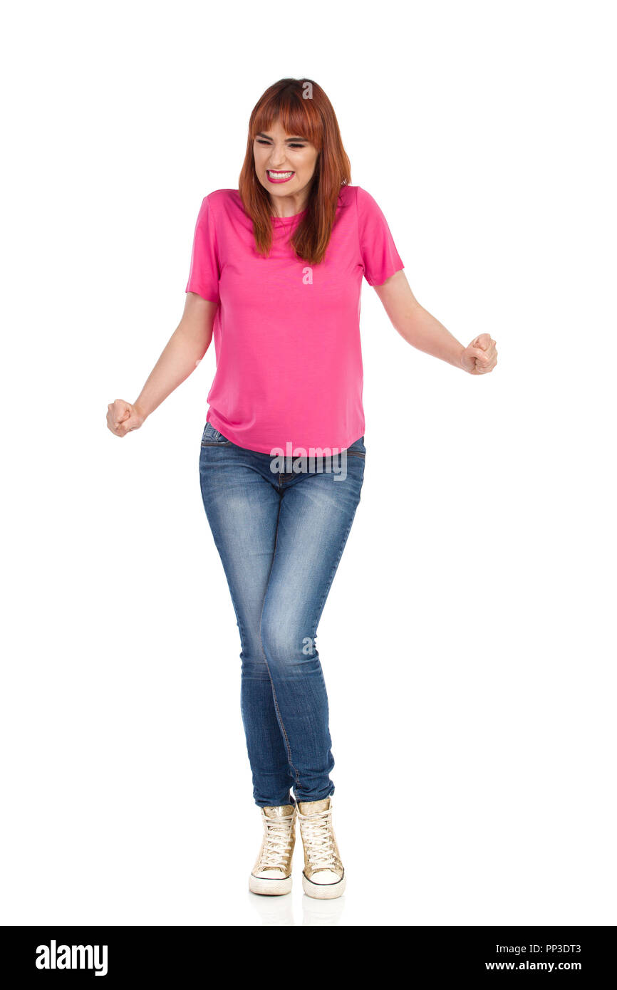 Angry young woman in pink t-shirt, jeans and gold sneakers is clenching fists and grimacing. Full length studio shot isolated on white. - Stock Image