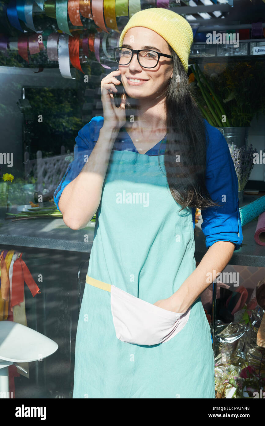 Flower Shop Girl Speaking by Phone - Stock Image
