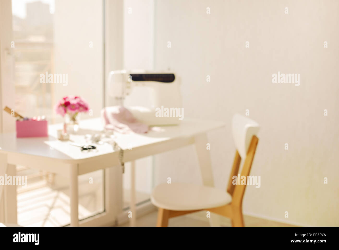 Workplace for sewing and needlework in a bright room with white furniture. Blurring effect and selective focus. - Stock Image