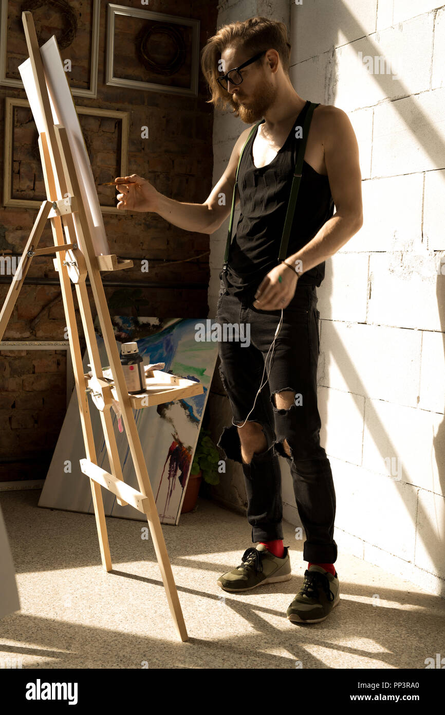 Inspired Male Artist Painting Picture on Easel - Stock Image