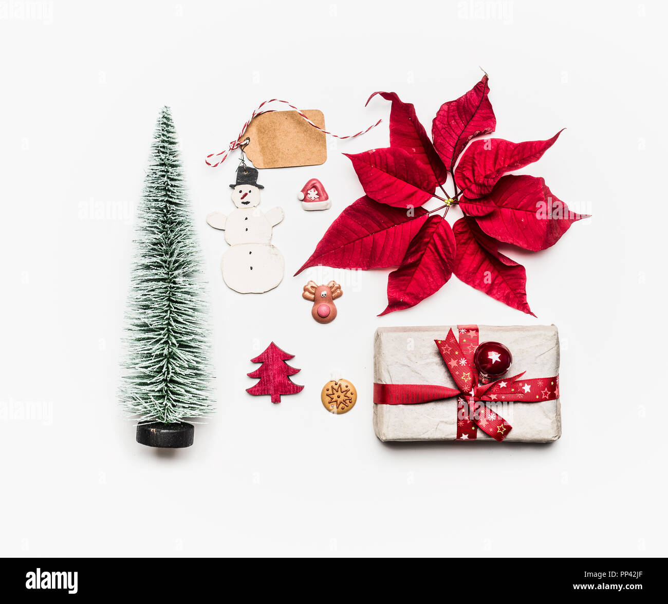 various holiday objects gift christmas tree decorations red poinsettia snowman tags on white background flat lay top view