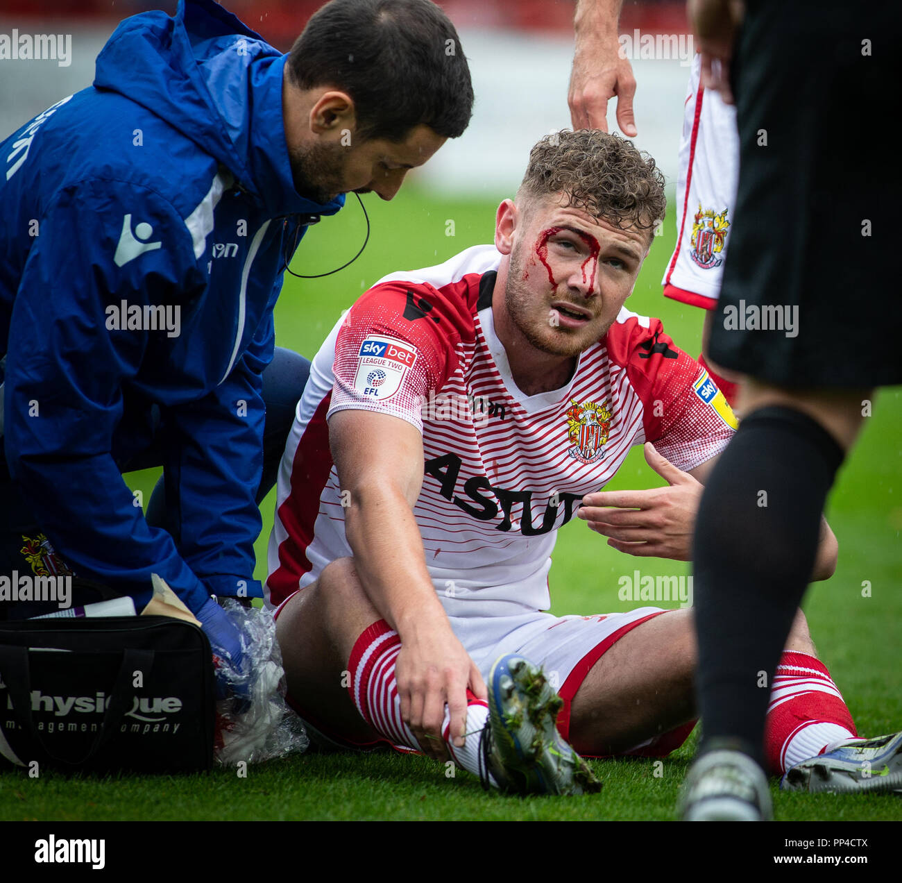 Football / soccer player receiving treatment for injury of cut above the eye football / soccer during match. - Stock Image