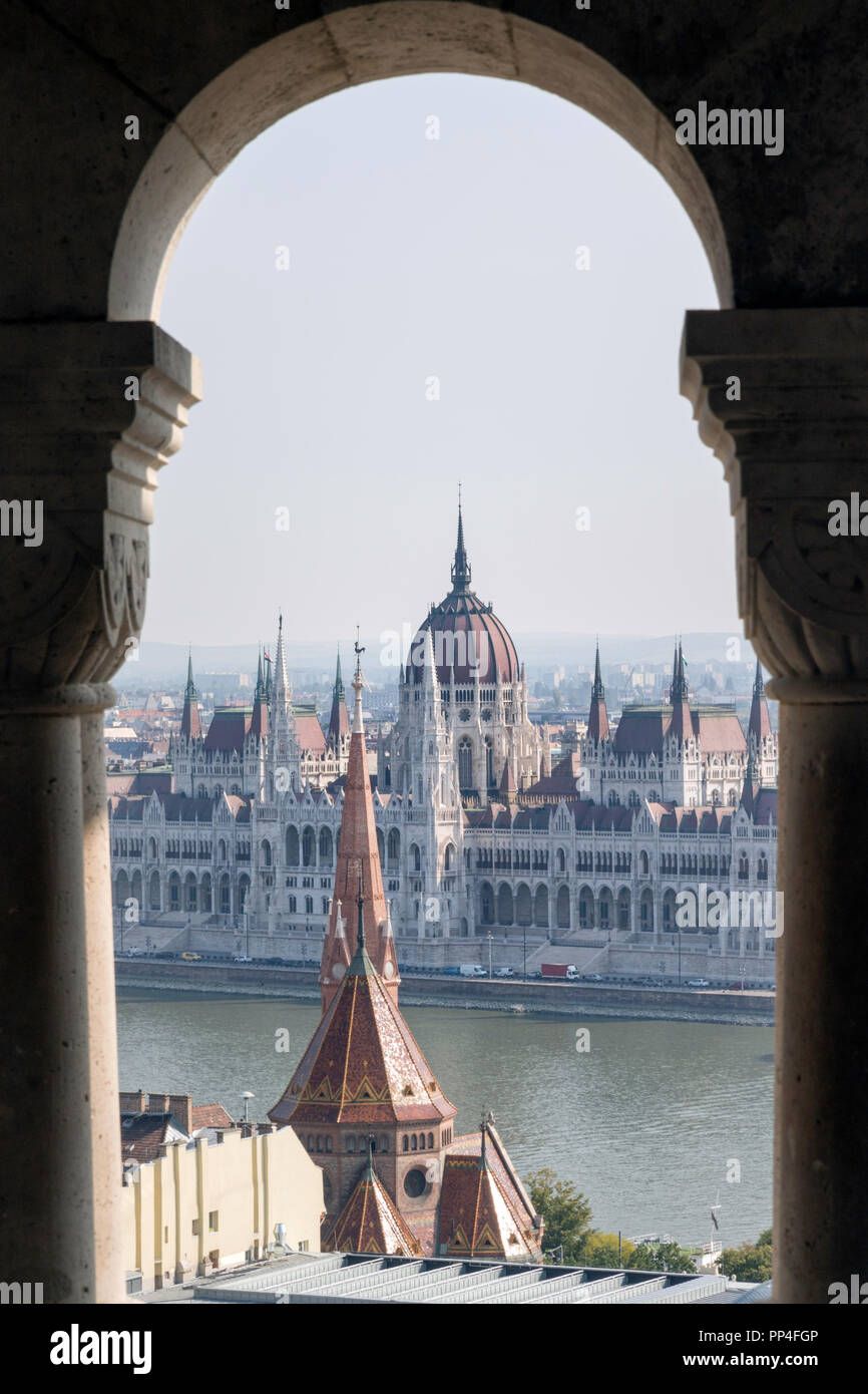 The Hungarian Parliament building seen through the arches of Fishermen's Bastion on Budapest's Castle Hill Stock Photo