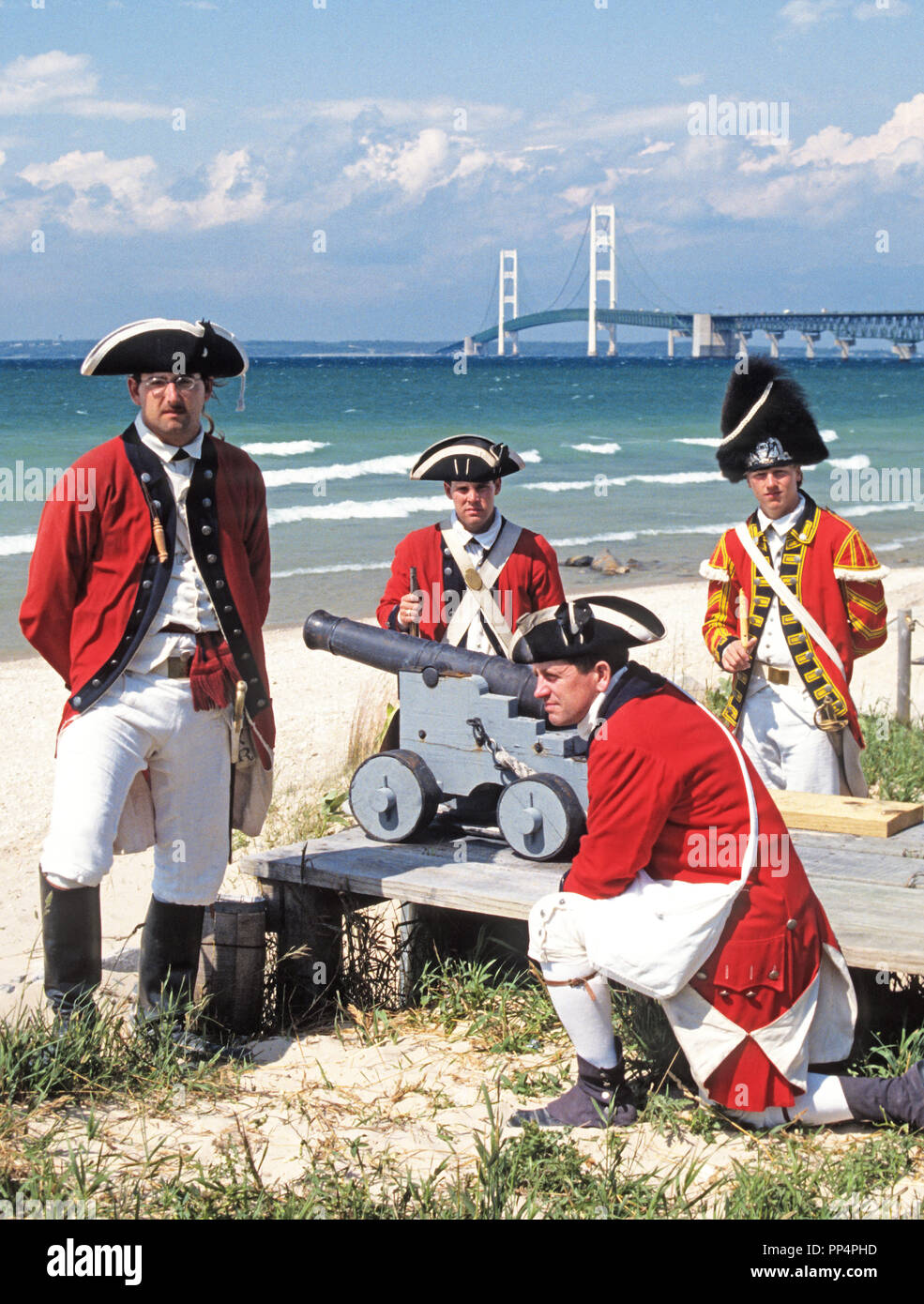 British Soldiers of King's 8th Regiment on Foot reenactment 1774-1781 occupation of Fort Michilimackinac, Michigan, with Mackinac Bridge in backgrnd. - Stock Image
