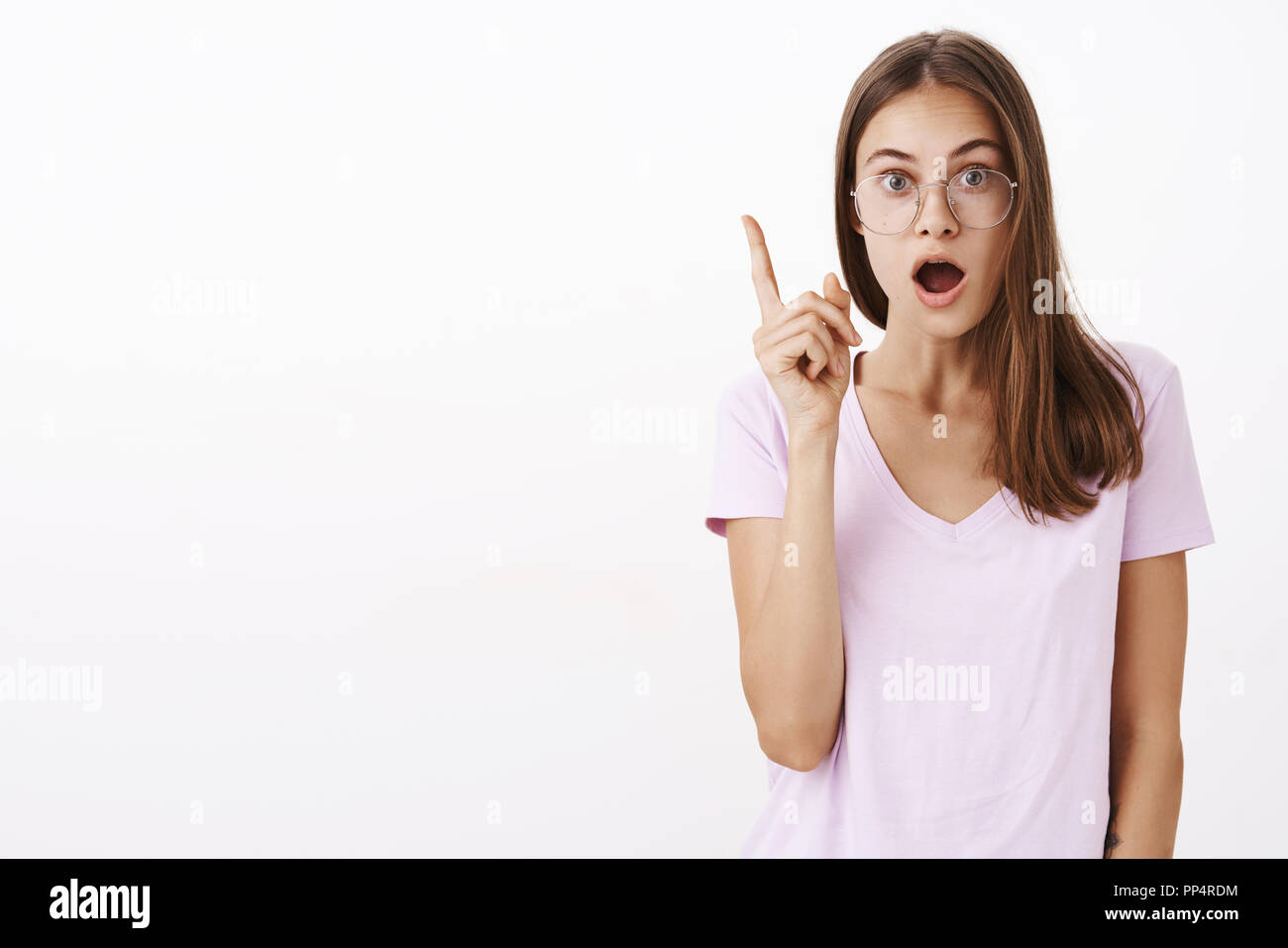 I got excellent suggestion. Smart and creative excited good-looking girl in glasses opening mouth while telling eureka raising index finger thinking up perfect plan against white background - Stock Image