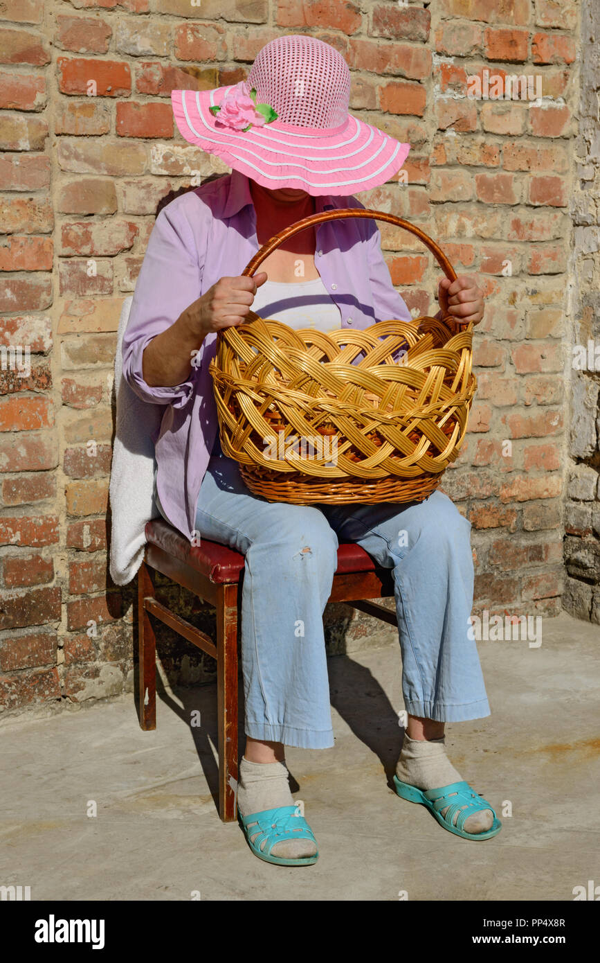 Close-up full length portrait of mature woman in wide-brimmed hat that is  sitting on the chair bowing her head over big wicker basket on her knees in 8422806221e8
