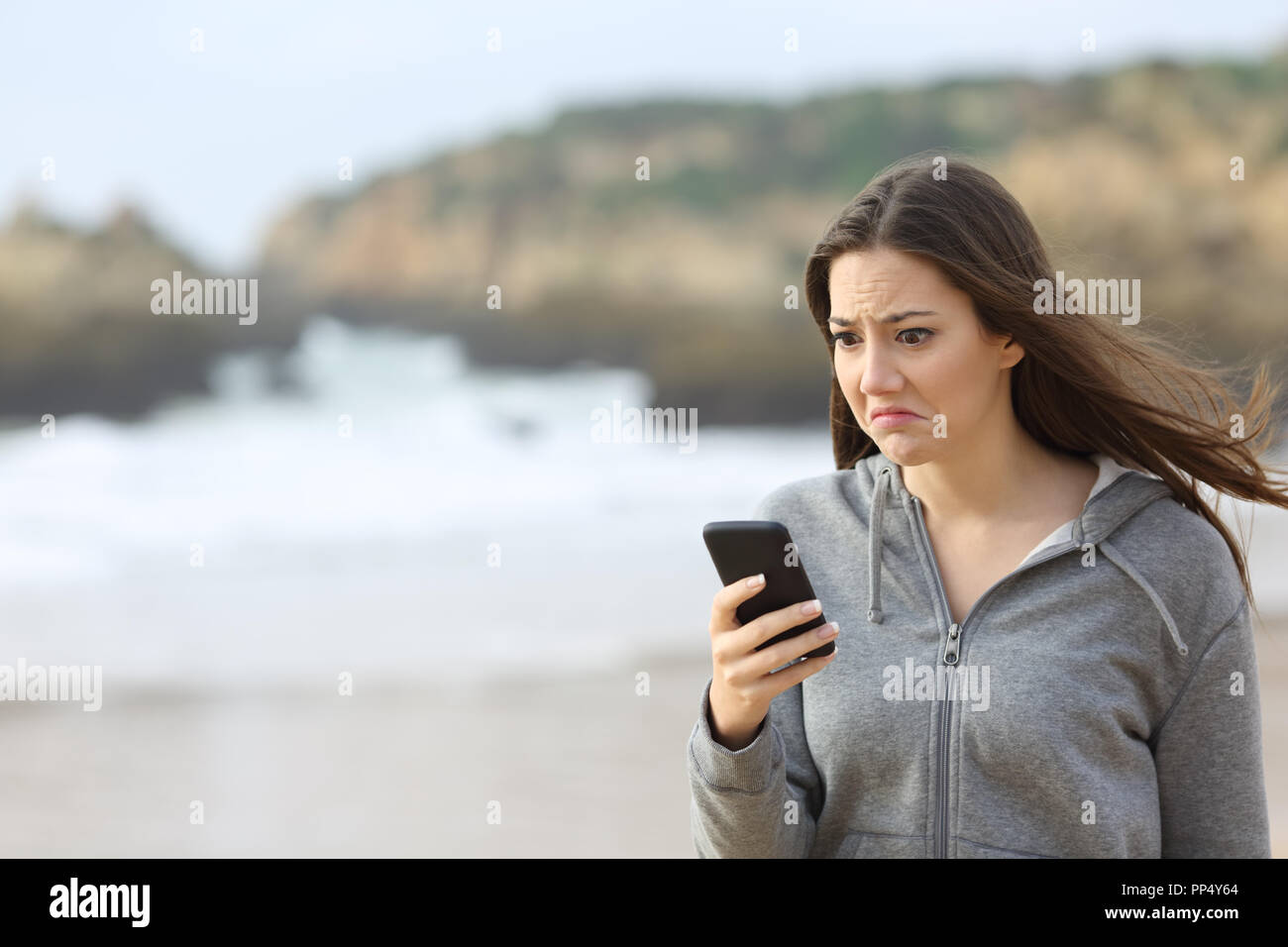 Disappointed teen reading phone message and grimacing walking on the beach - Stock Image