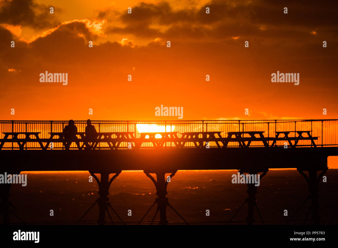 Aberystwyth Wales UK, Sunday 23 September 2018  UK Weather:  A fiery sunset over the seaside pier on Equinox Sunday evening in Aberystwyth on the west wales coast.  Today was the last day of Astronomical Summer - when the days and night are of equal lengths. From tomorrow the nights are longer than the days, marking  the onset of Astronomical Winter in the northern hemisphere  Photo © Keith Morris / Alamy Live News Stock Photo