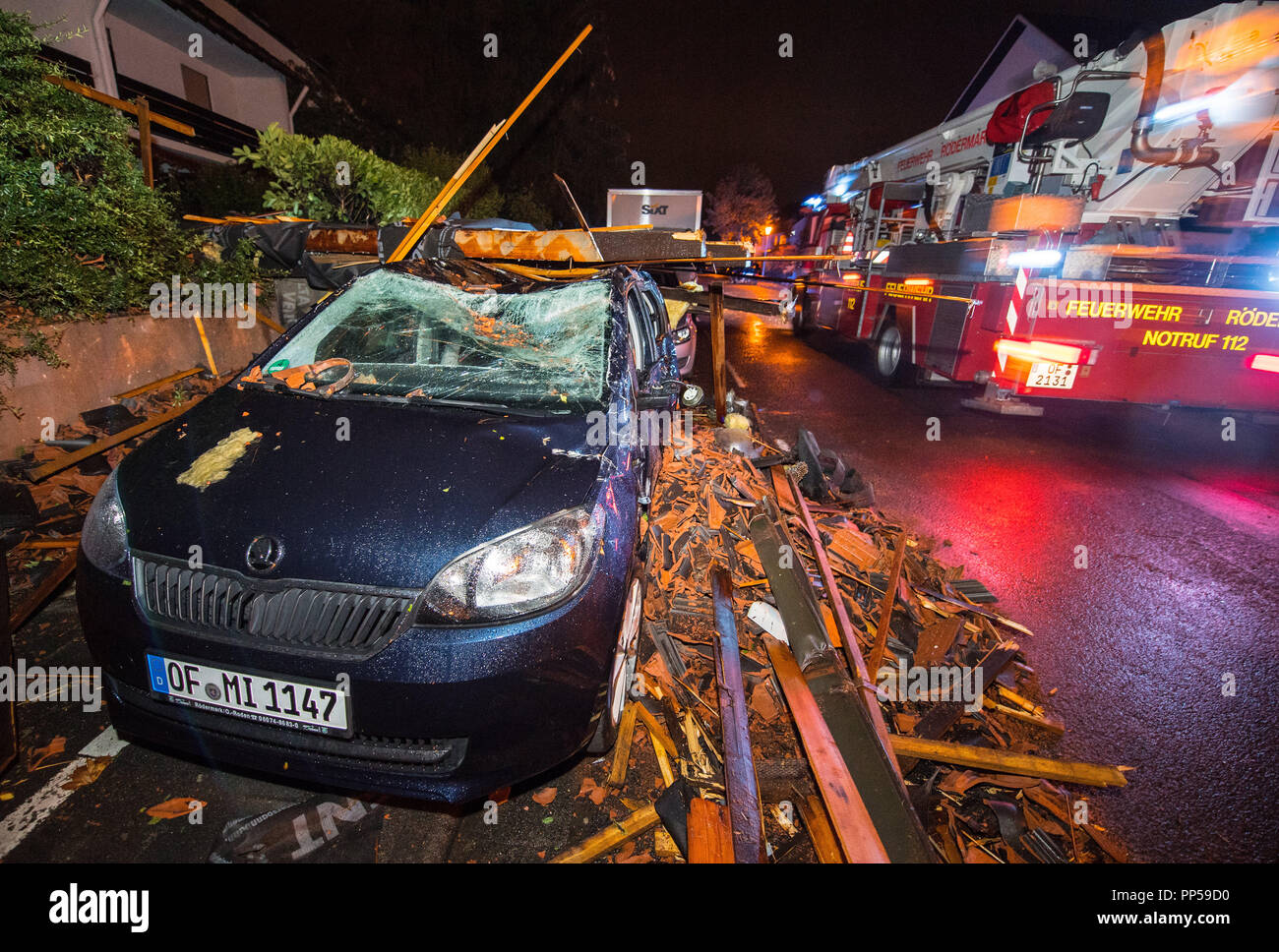 Roedermark, Hessen. 23rd Sep, 2018. A fire engine passing a badly damaged car with its roof pressed in and windshield destroyed. According to a resident, a very strong gust of wind dragged a house roof and hurled it onto the opposite side of the street. A car parked there was completely buried under the rubble and severely damaged. Credit: Andreas Arnold/dpa/Alamy Live News - Stock Image