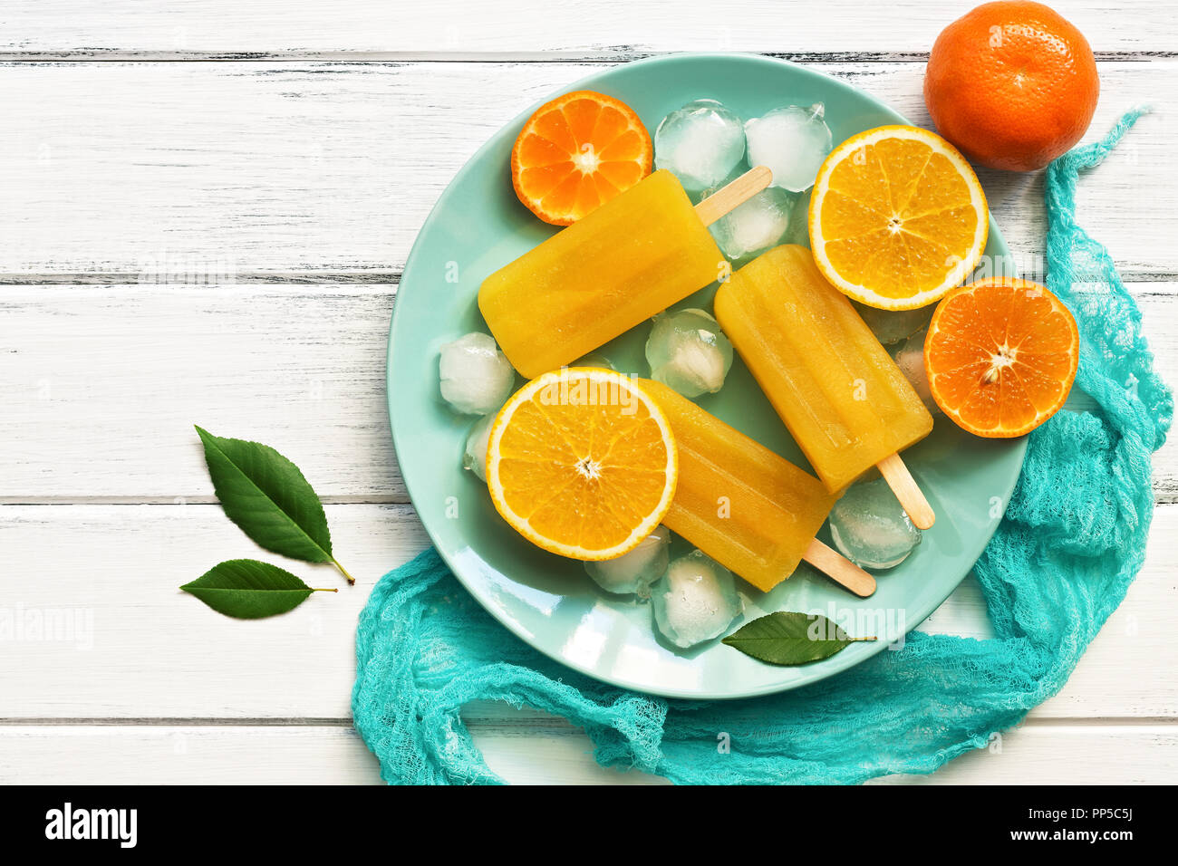 Orange Tangerine popsicles in blue plate with ice cubes and slices of fruit, white wooden rustic background. Top view, copy space - Stock Image