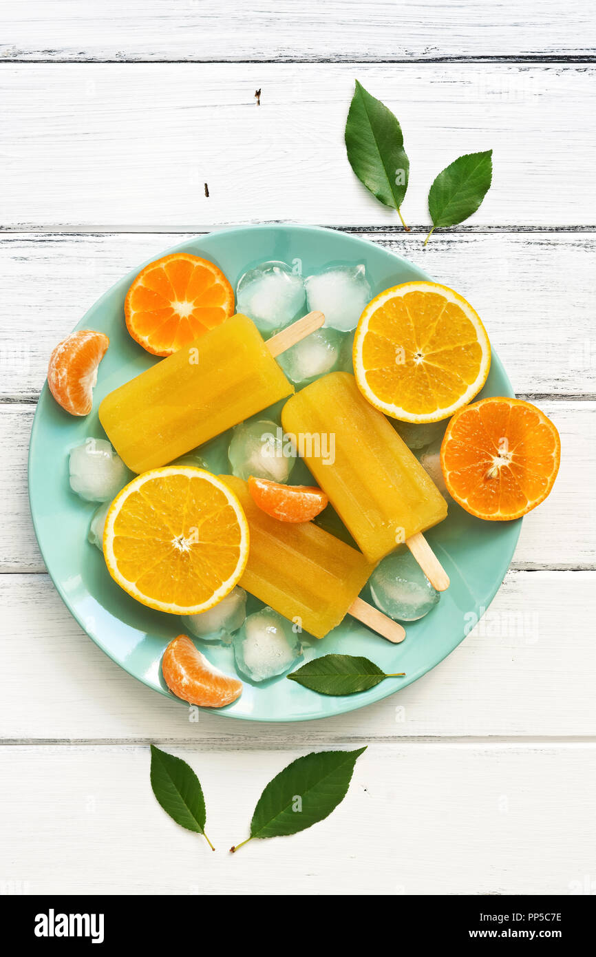 Orange Tangerine popsicles in blue plate with ice cubes and slices of fruit, white wooden rustic background. Top view, copy space,flat lay. Stock Photo