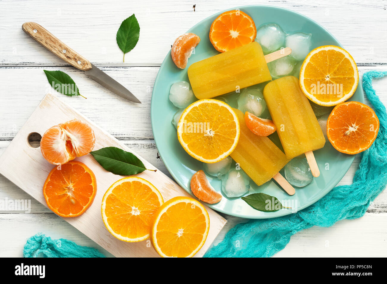 Orange Tangerine popsicles in blue plate with ice cubes and slices of fruit, white wooden rustic background. Top view, copy space,flat lay. - Stock Image