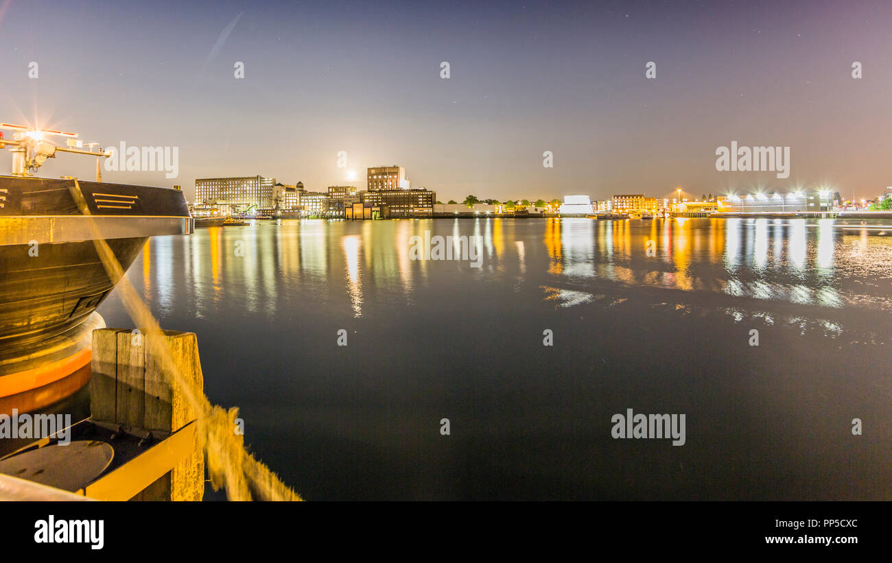 beautiful view of the canal and a part of the city of Rotterdam in the netherlands at night with beautiful reflection on the water of the lights - Stock Image