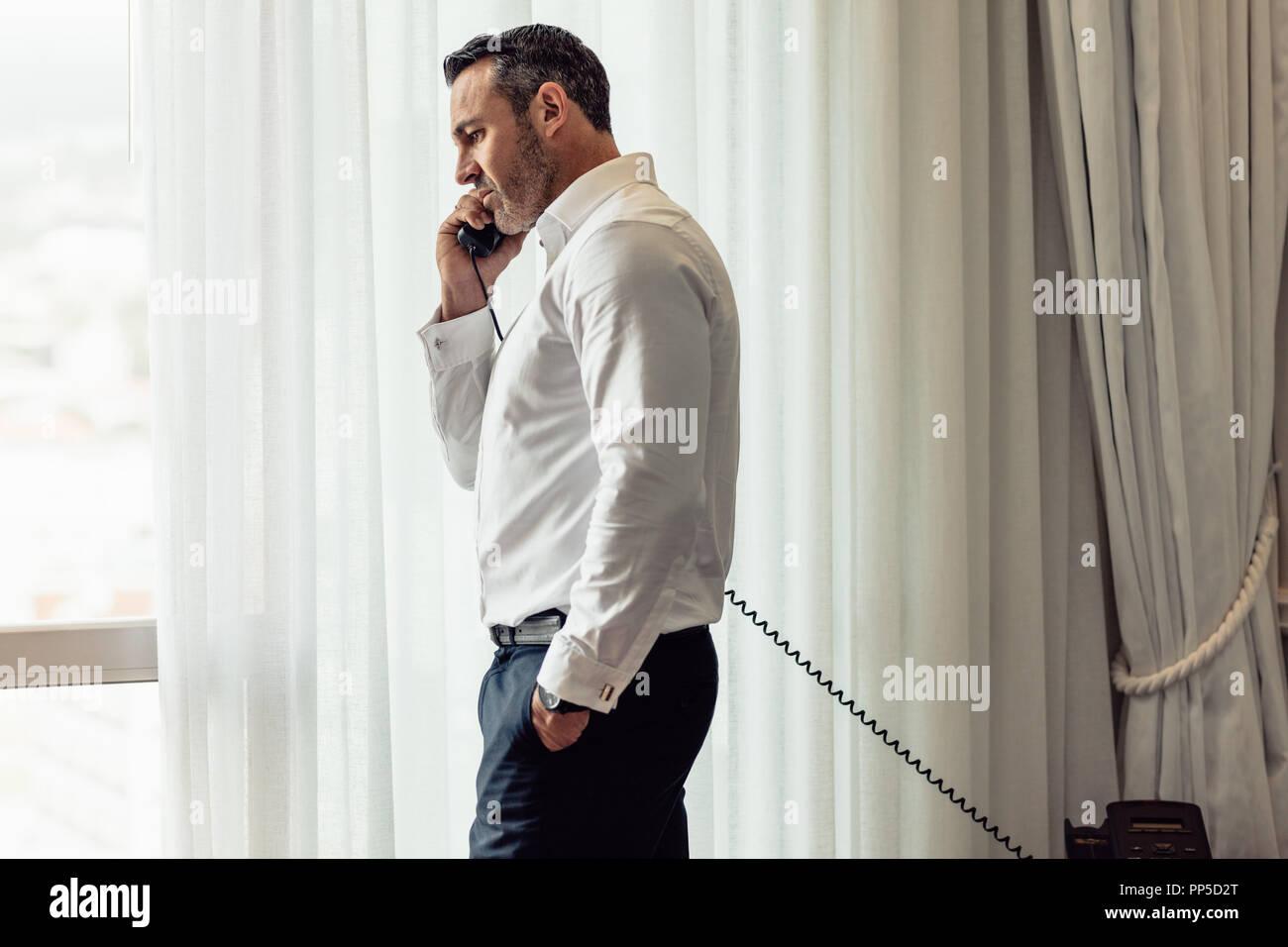 Businessman in formals talking over landline phone. Handsome businessman making call from hotel room. - Stock Image