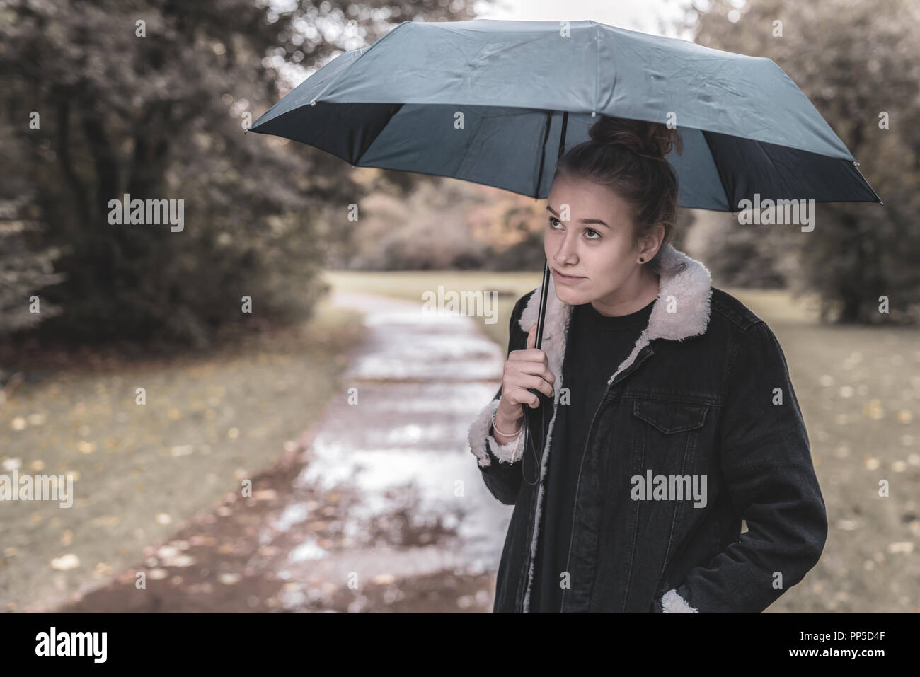 A young woman with an umbrella is waiting for better weather in a park - Stock Image