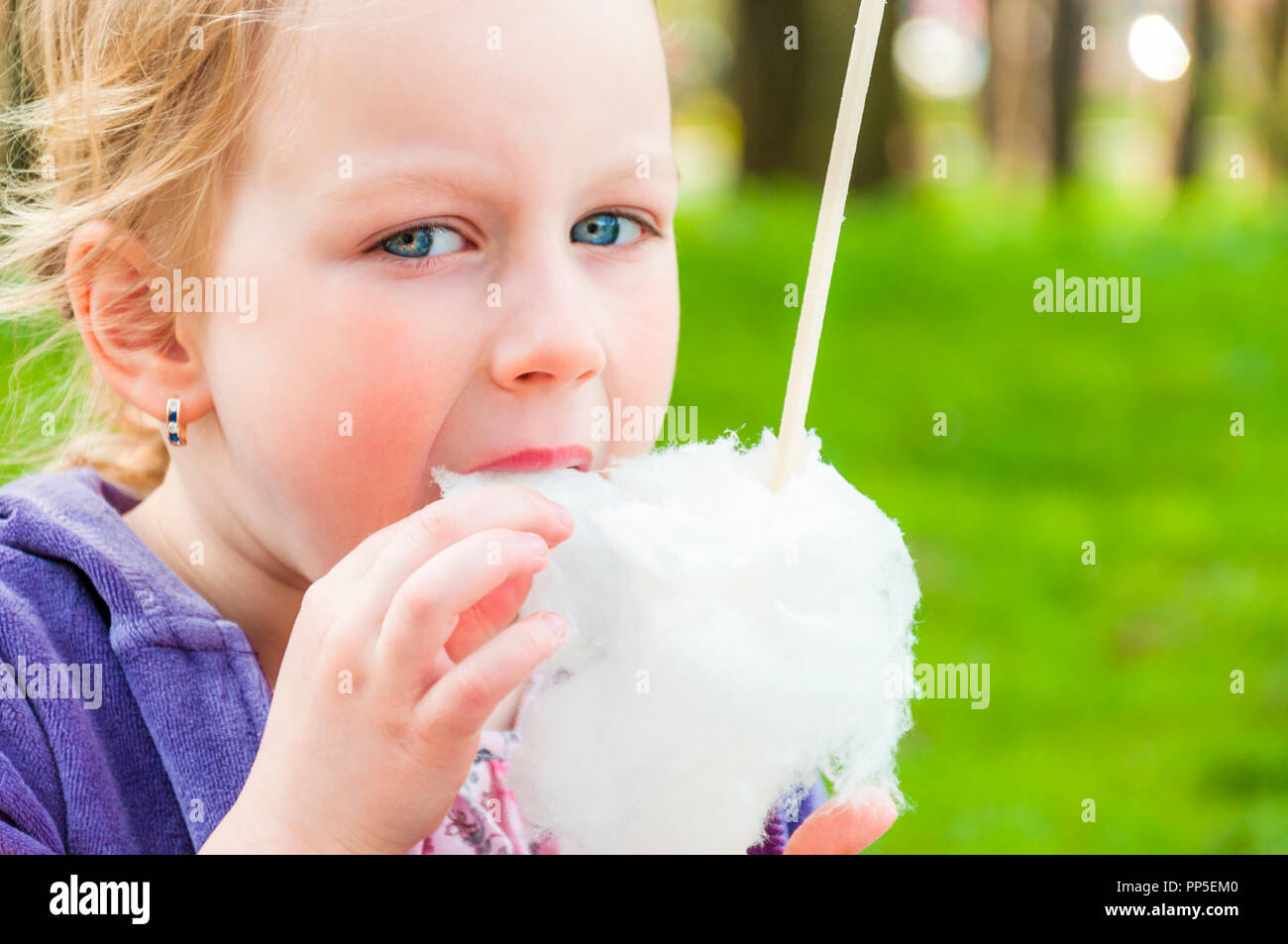The photograph shows blue-eyed blonde girl that eating candy-floss turned upside down and making it with love and inherent to children passion. - Stock Image