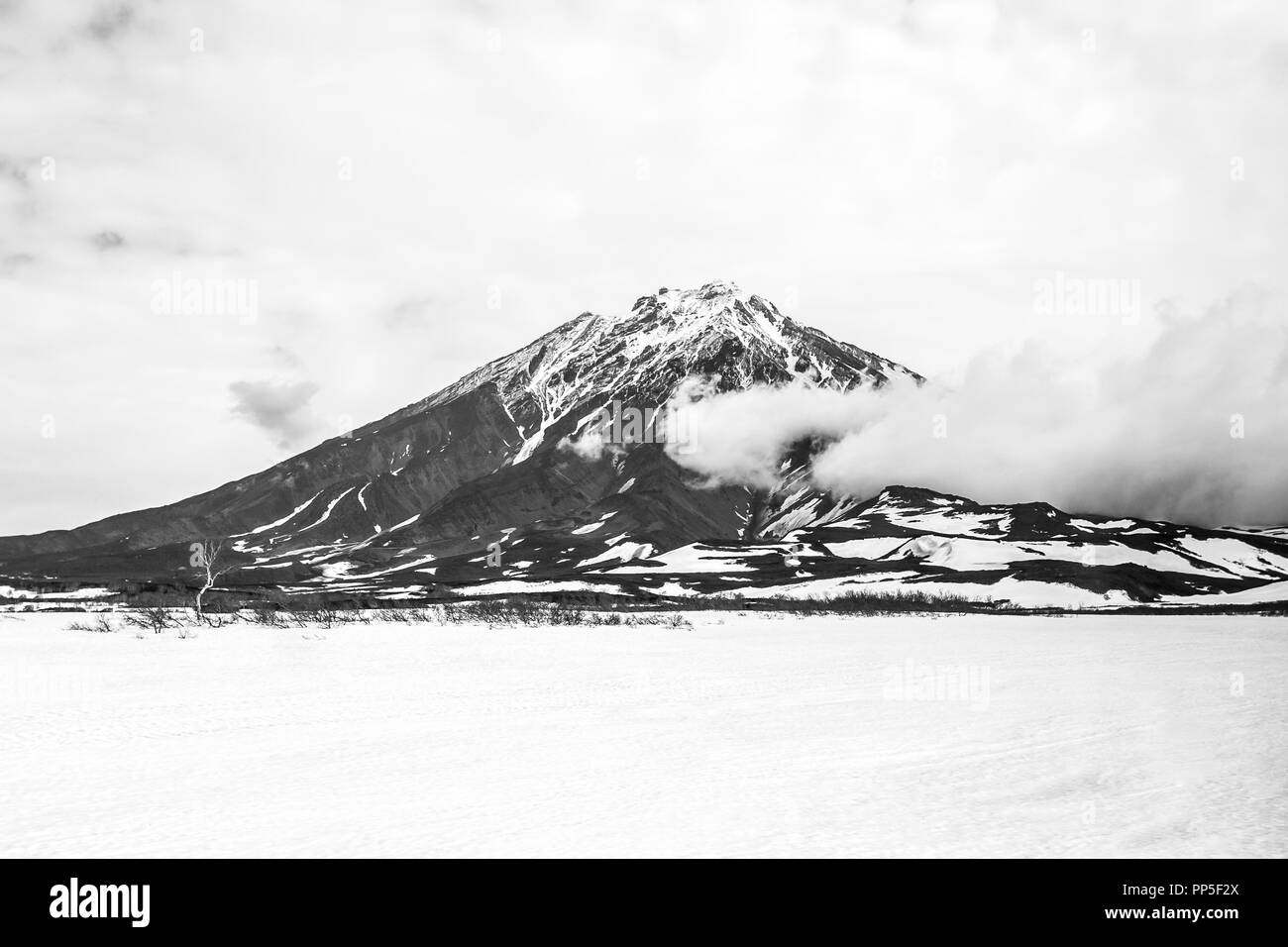 View of the Volcano Koryaksky in overcast weather, Kamchatka Peninsula, Russia - Stock Image