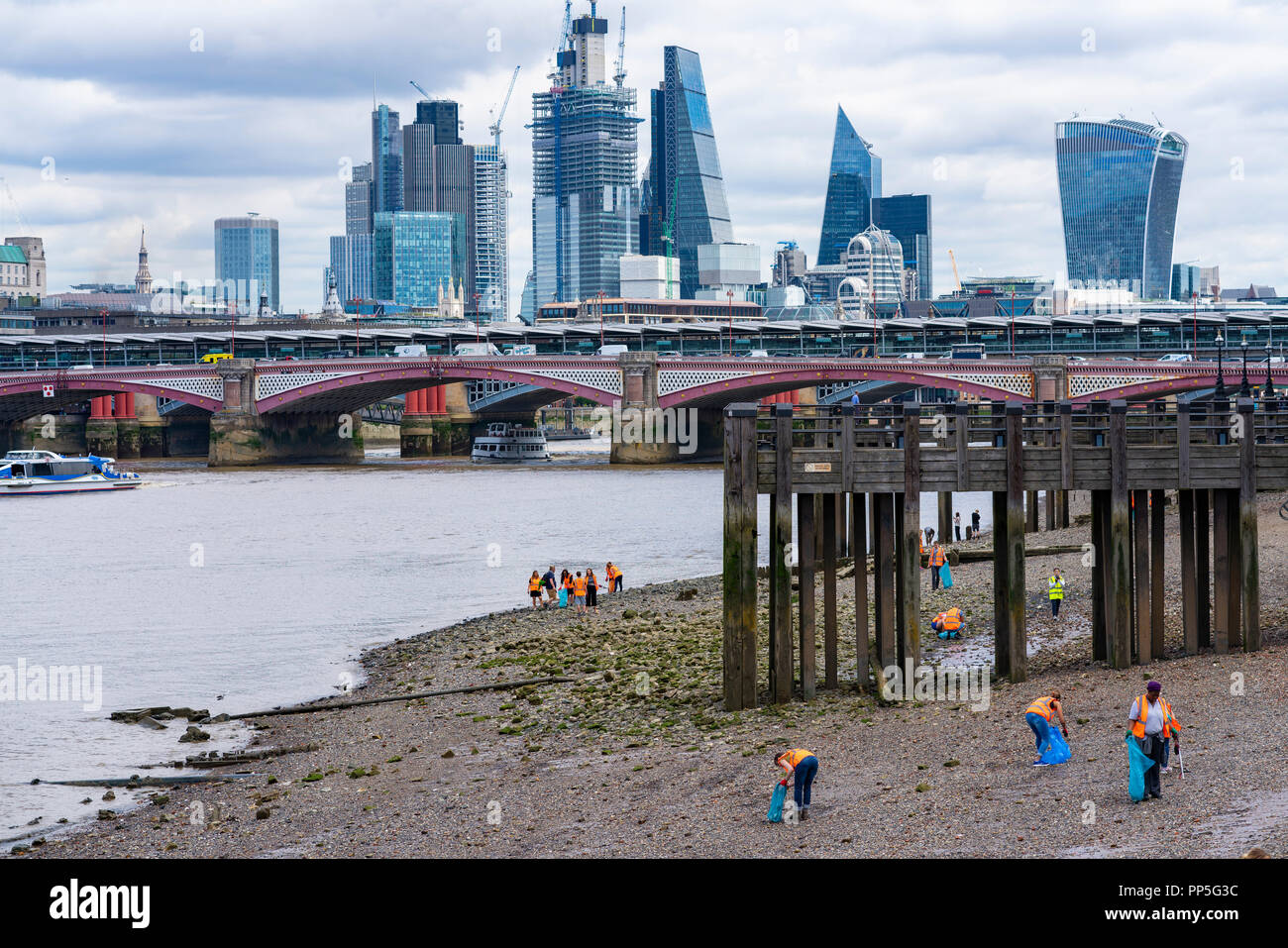 Volunteers cleaning the shores of the Thames from waste during low tide, Southbank, London - Stock Image