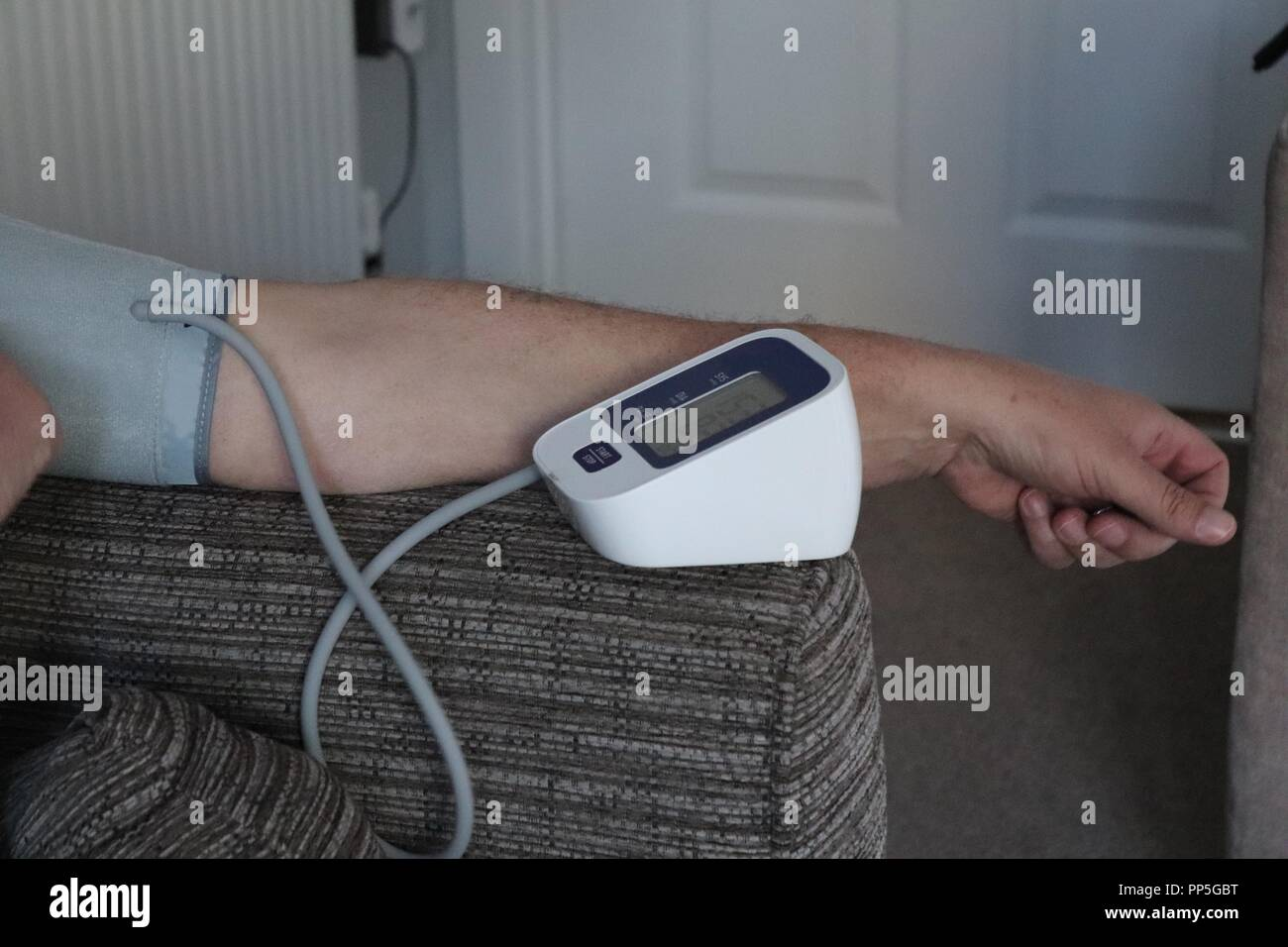 Blood pressure machine in the home.test blood systolic and diastolic pressure.adult arm relaxed at home - Stock Image