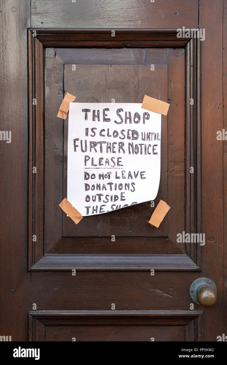 Hand written shop closed notice taped to door - Stock Image