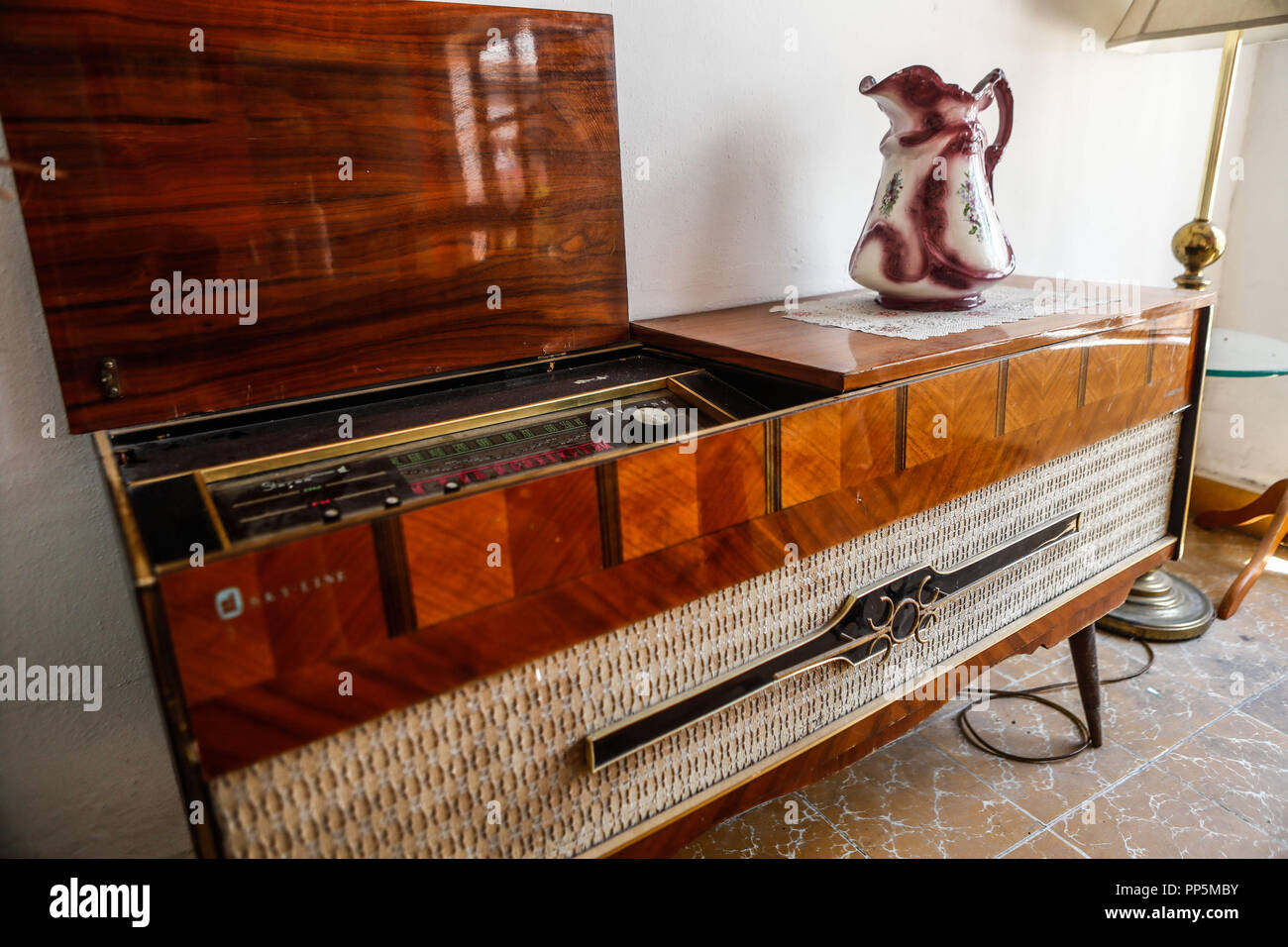 Classic Vinyl Record Player With Radio. AM radio, FM, Tune frequency of radio stations. Wooden furniture. Classic furniture Ceramic decorative vase an - Stock Image