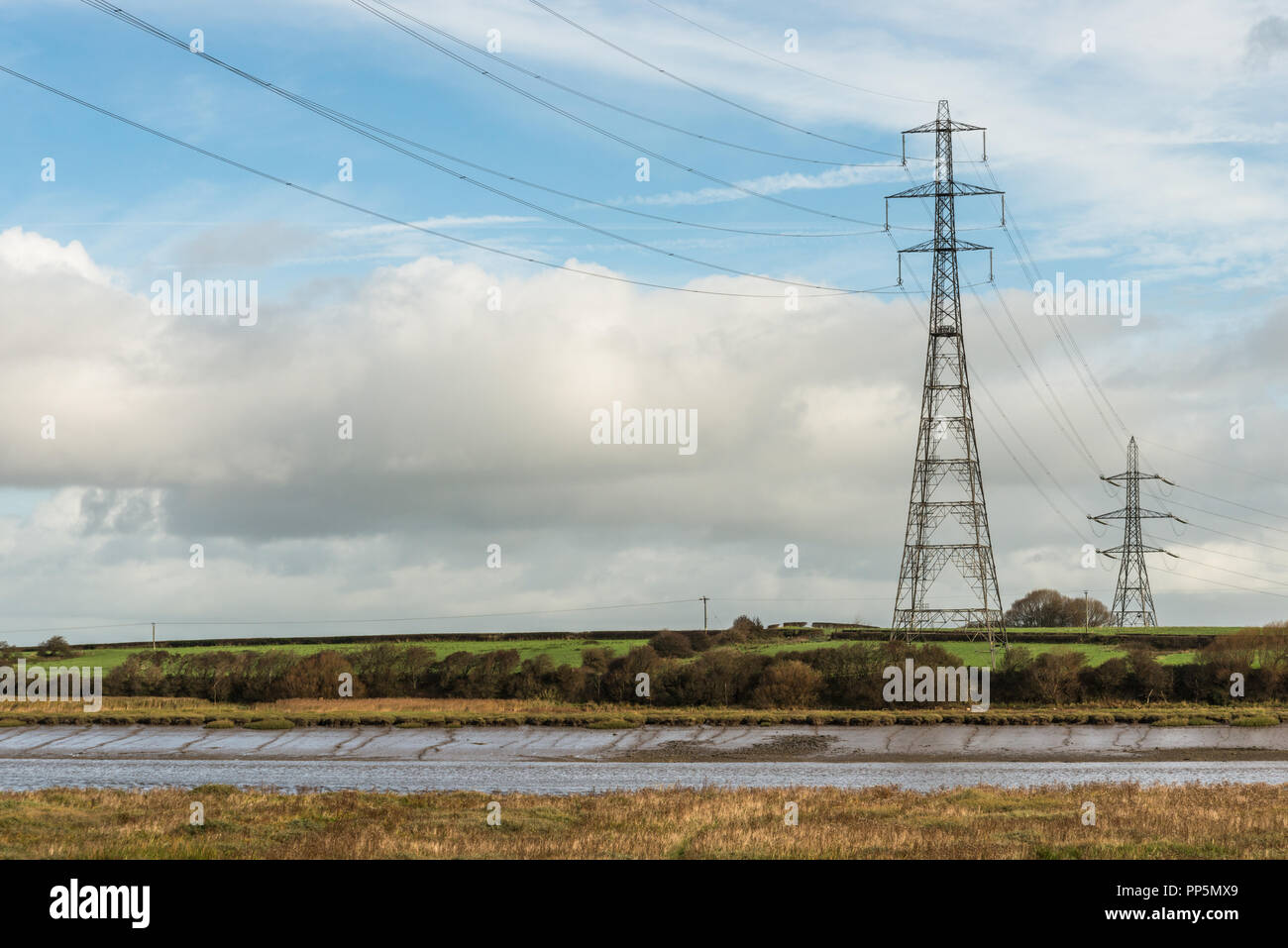 Two pylons on the side of the River Wyre in Lancashire, England, UK with high voltage cables crossing the water in the countryside. - Stock Image