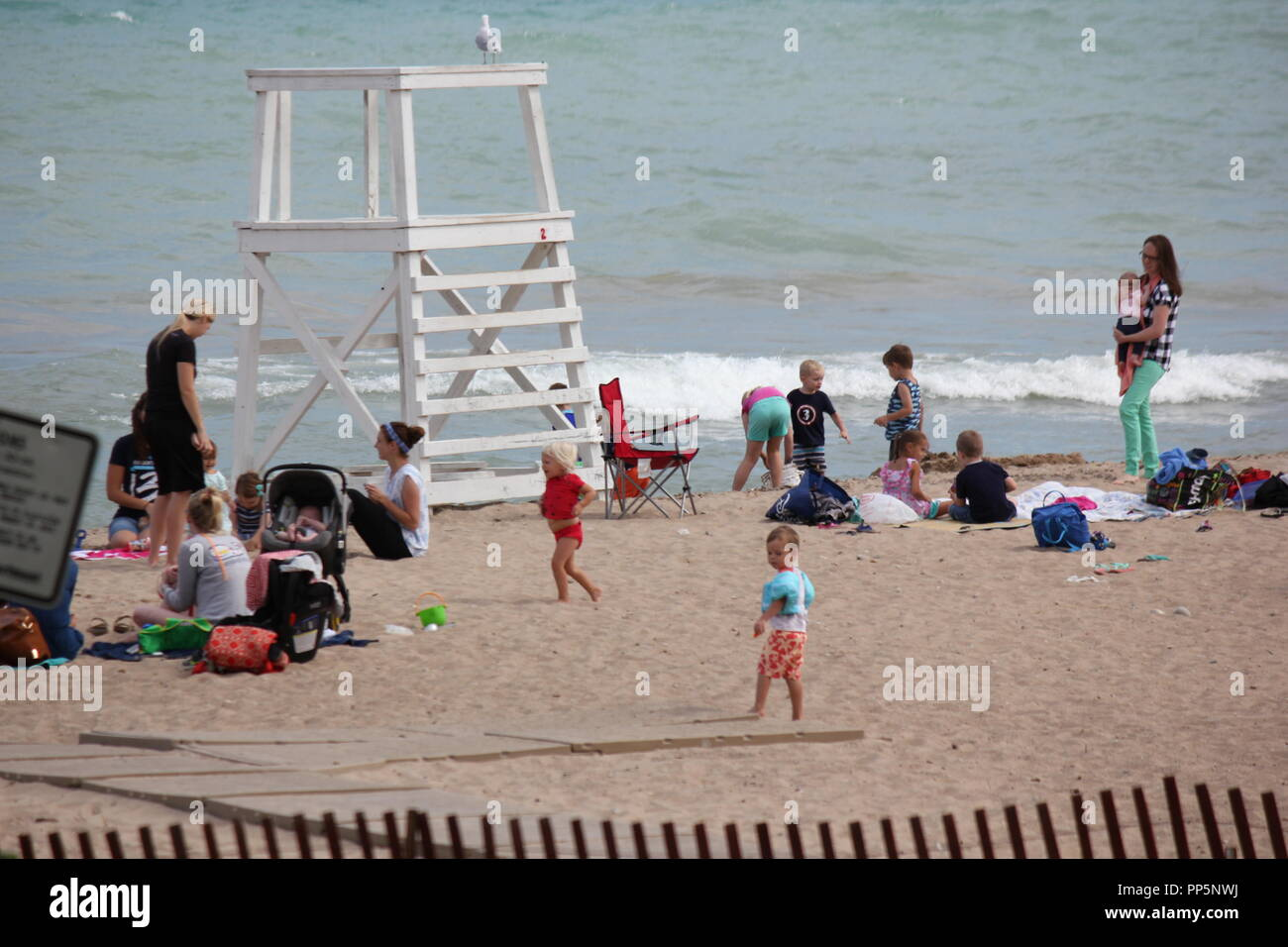 Modern summer lifestyle imagery of women enjoying the beach with their young children, beach scene. - Stock Image