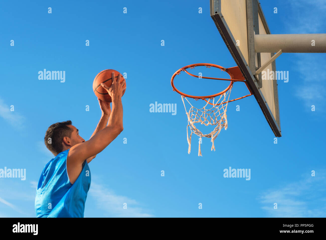 Street basketball athlete performing slam dunk on the court - Stock Image