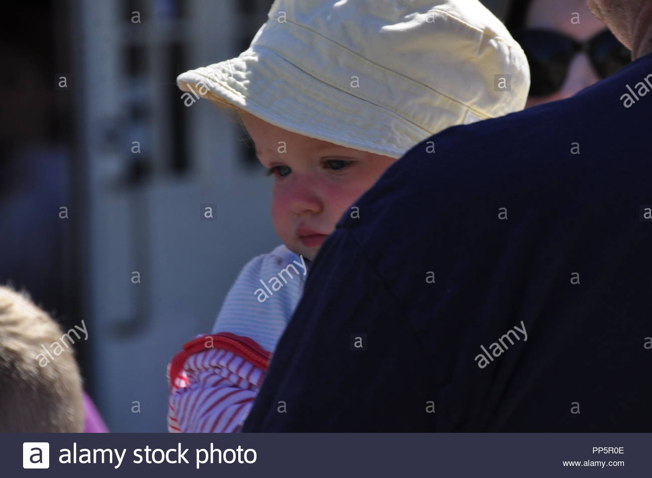 This fair-skinned baby being held by her father was seen at the Kimmel Orchard Apple Festival in Nebraska City, Nebraska. - Stock Image