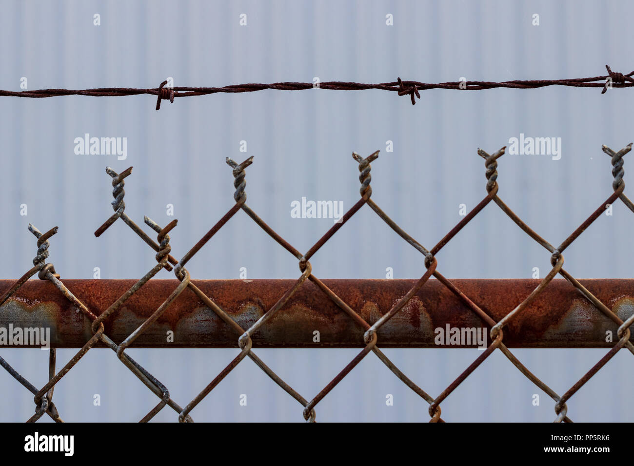 Old Rusty Chain Link Barbed Wire Fence With White Wall Stock Photo Alamy