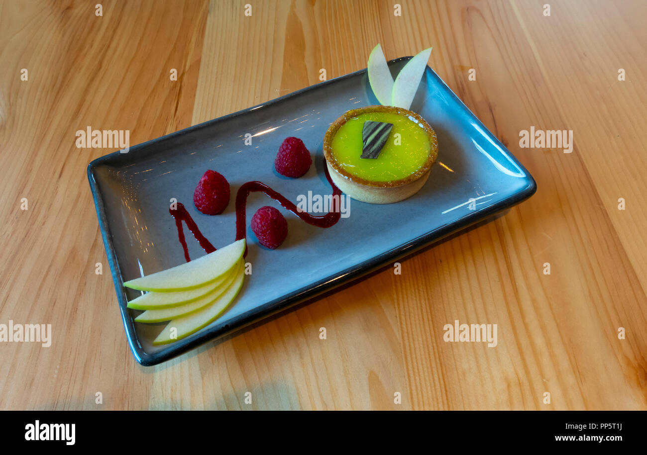 A Key Lime tart with a few raspberries  and sliced apple on a rectangular blue dish - Stock Image