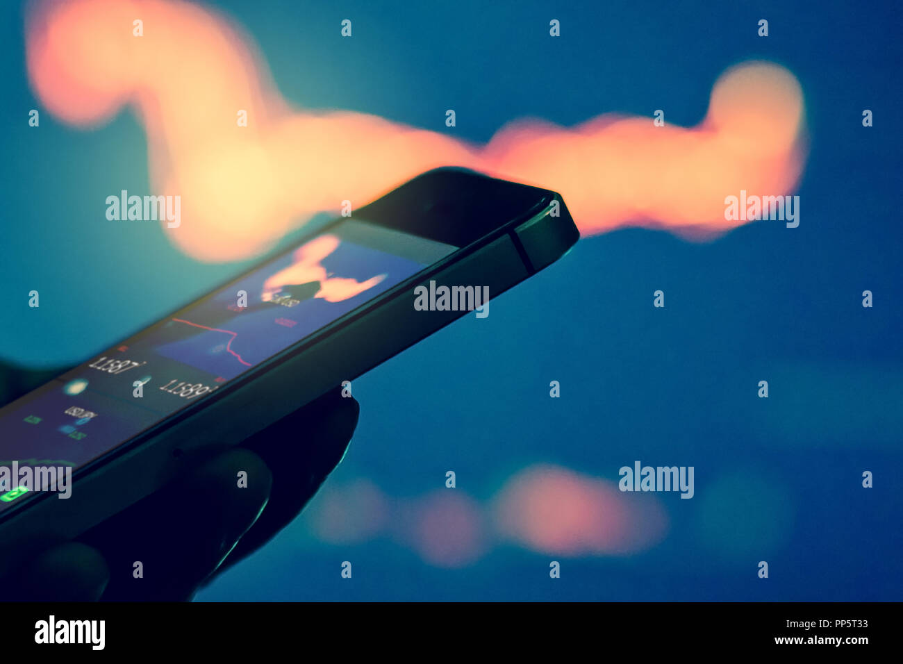Trader in dark using mobile phone against stock market charts Stock Photo