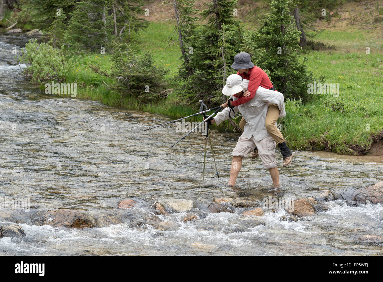 Man carrying woman across a stream on a backpack trip in Oregon's Wallowa Mountains. - Stock Image