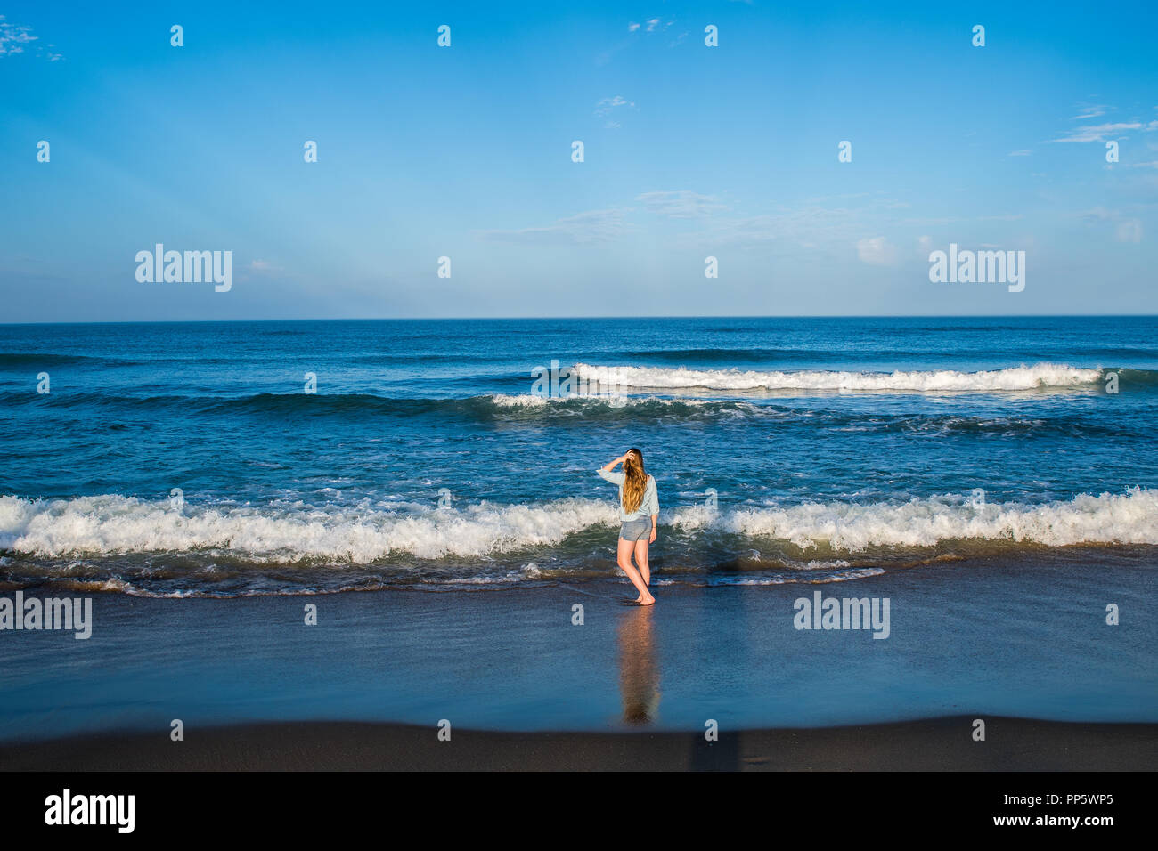 A little girl plays in the surf along the oceanfront of the outer banks in North Carolina Stock Photo