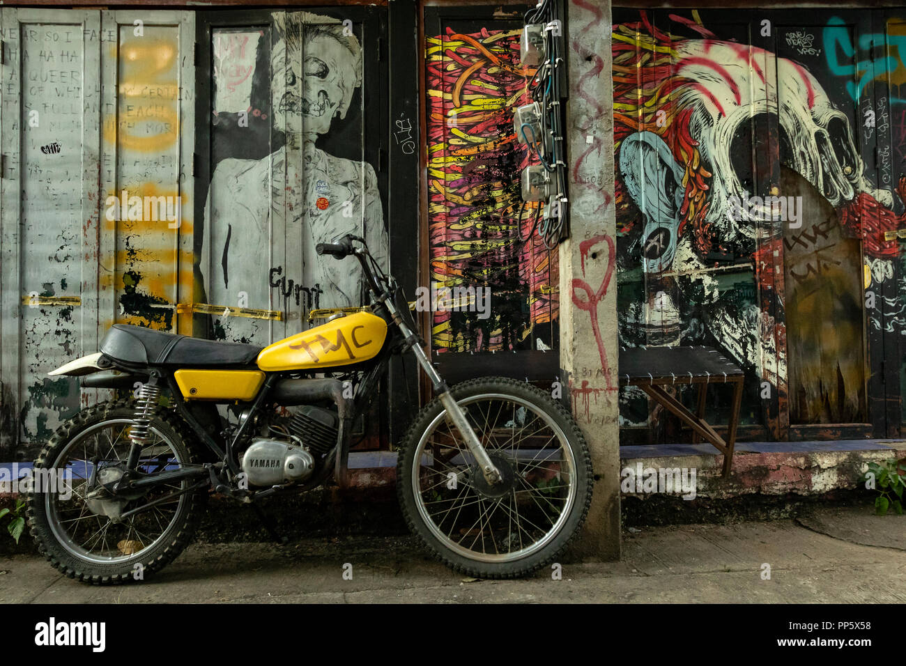 Motorbike parked with biker graffiti covered walls in Pai, Thailand - Stock Image